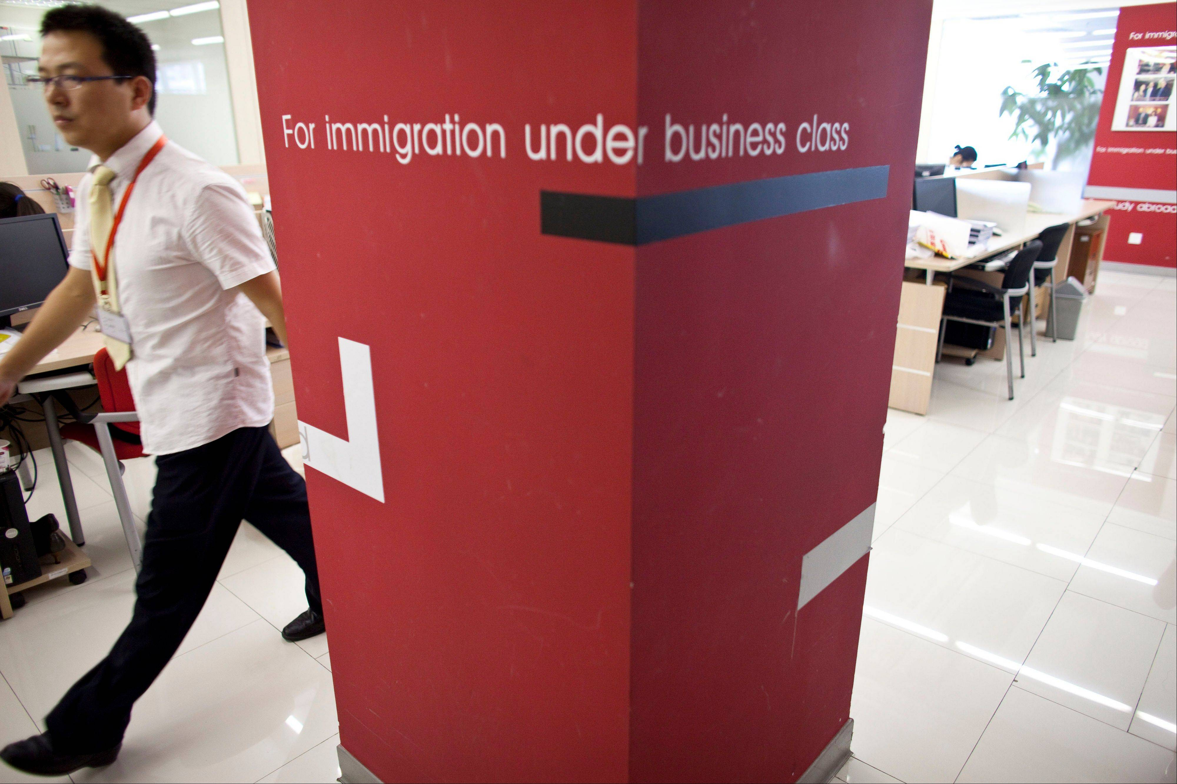 A worker walks inside an office of Beijing Goldlink Go-Abroad Consulting Co., an immigration consulting firm assisting Chinese to immigrate to Canada and the United States, in Beijing. Associated Press