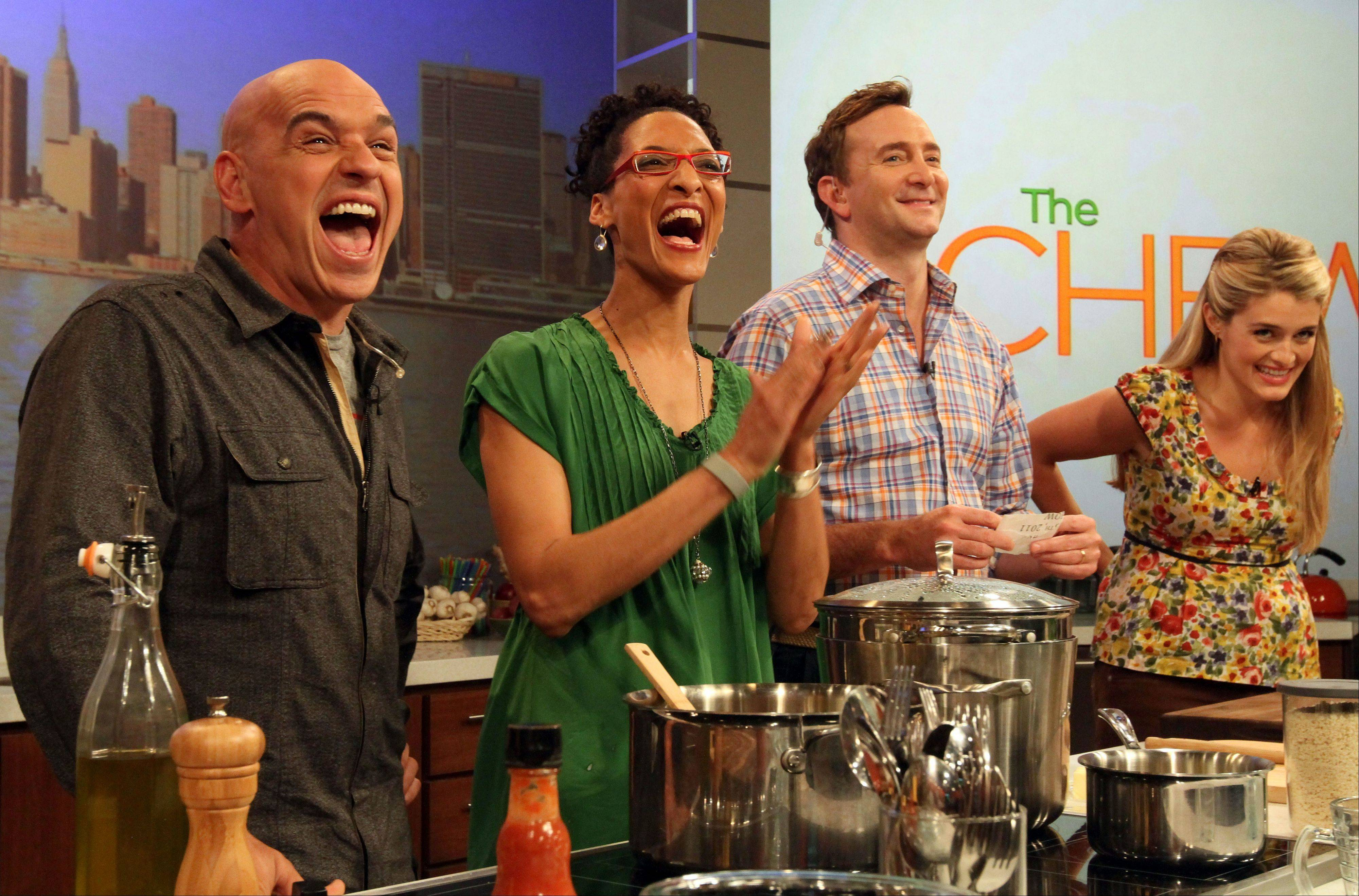 "During a recent taping of ""The Chew,"" Iron Chef Michael Symon, left, Carla Hall, Clinton Kelly and Daphne Oz react to audience applause during a rehearsal of the show in New York. ABC hopes these food and style stars help soap fans get over cancellation of their favorite stories."
