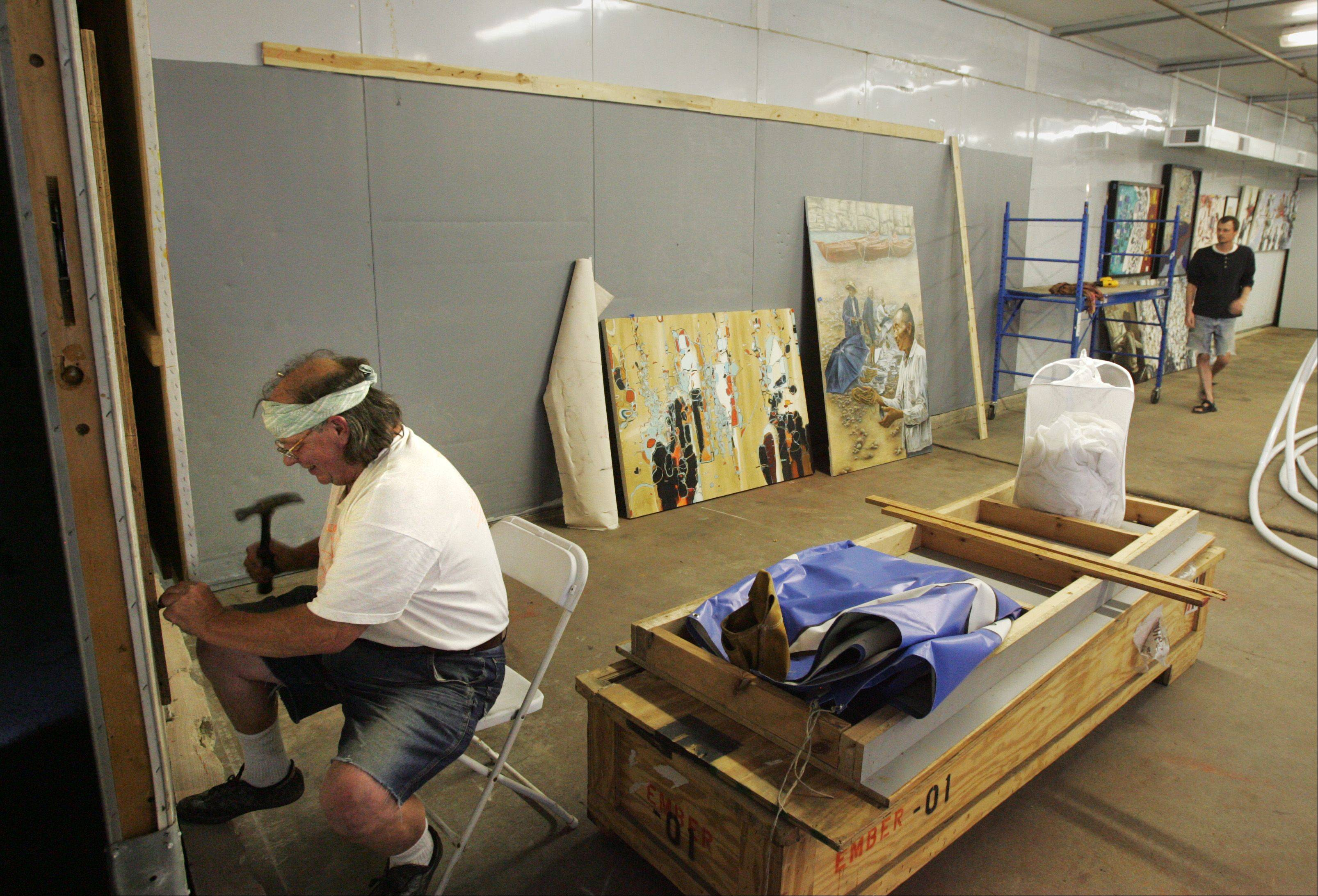 Artist David Powers, left, sets up a gallery exhibit in the Haight warehouse downtown Elgin. Helping out is oil painter Peter Zalesky, who is also showing his own work at The Next Wave Art Salon, which runs from 6 to 10 p.m. today and Saturday, Sept. 9 and 10.