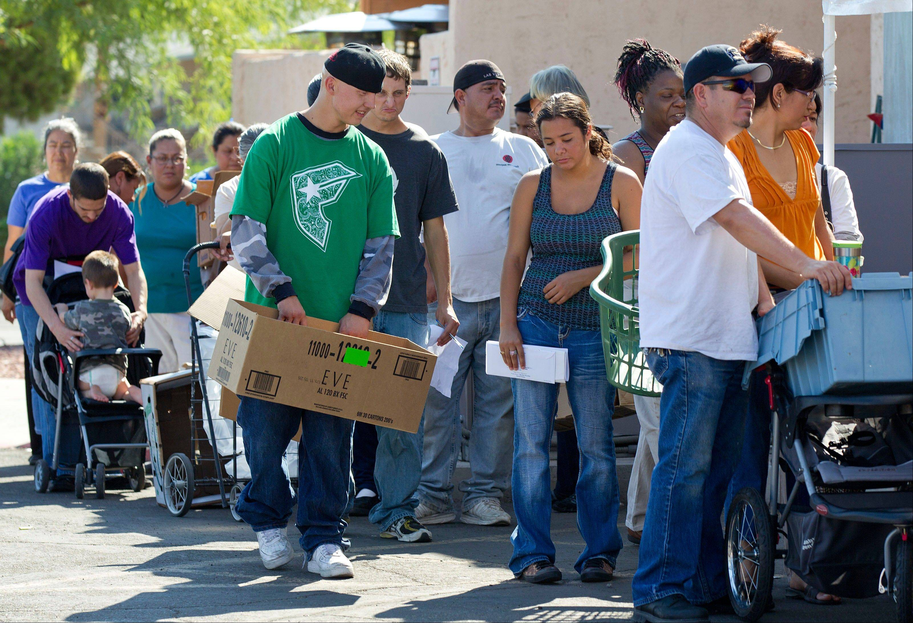People stand in line waiting to fill boxes with food at the Living Faith Assembly Church food pantry Wednesday in Las Vegas. There was hope on the jobs front Wednesday when it was reported companies in July advertised the most jobs in three years.