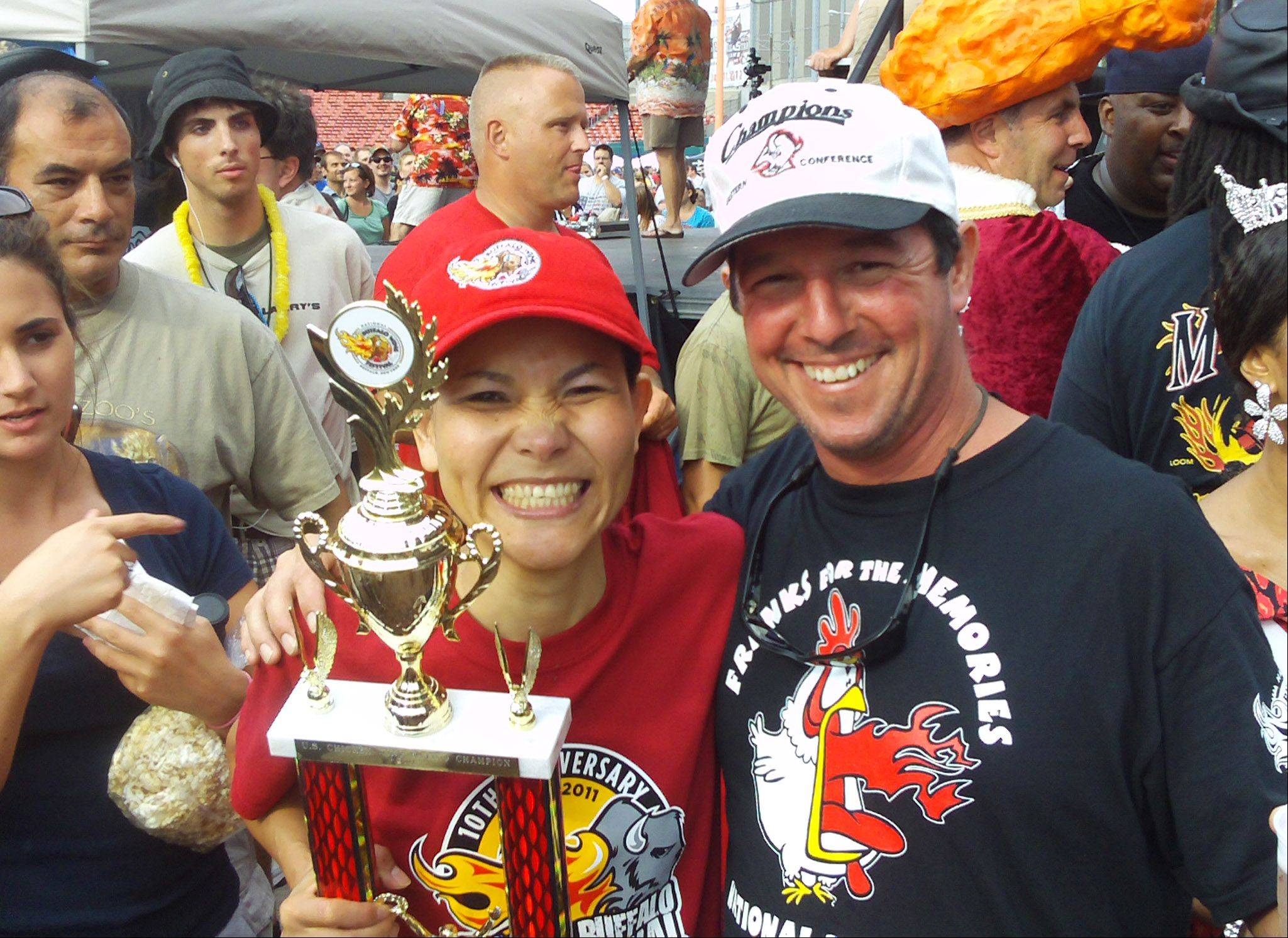"Jim Schultz Jr., right, owner of Franks for the Memories in Mundelein, poses with Sonya Thomas, winner of the National Buffalo Wing Festival's wing eating contest. Thomas, better known as ""The Black Widow"", ate 183 wings in 12 minutes."