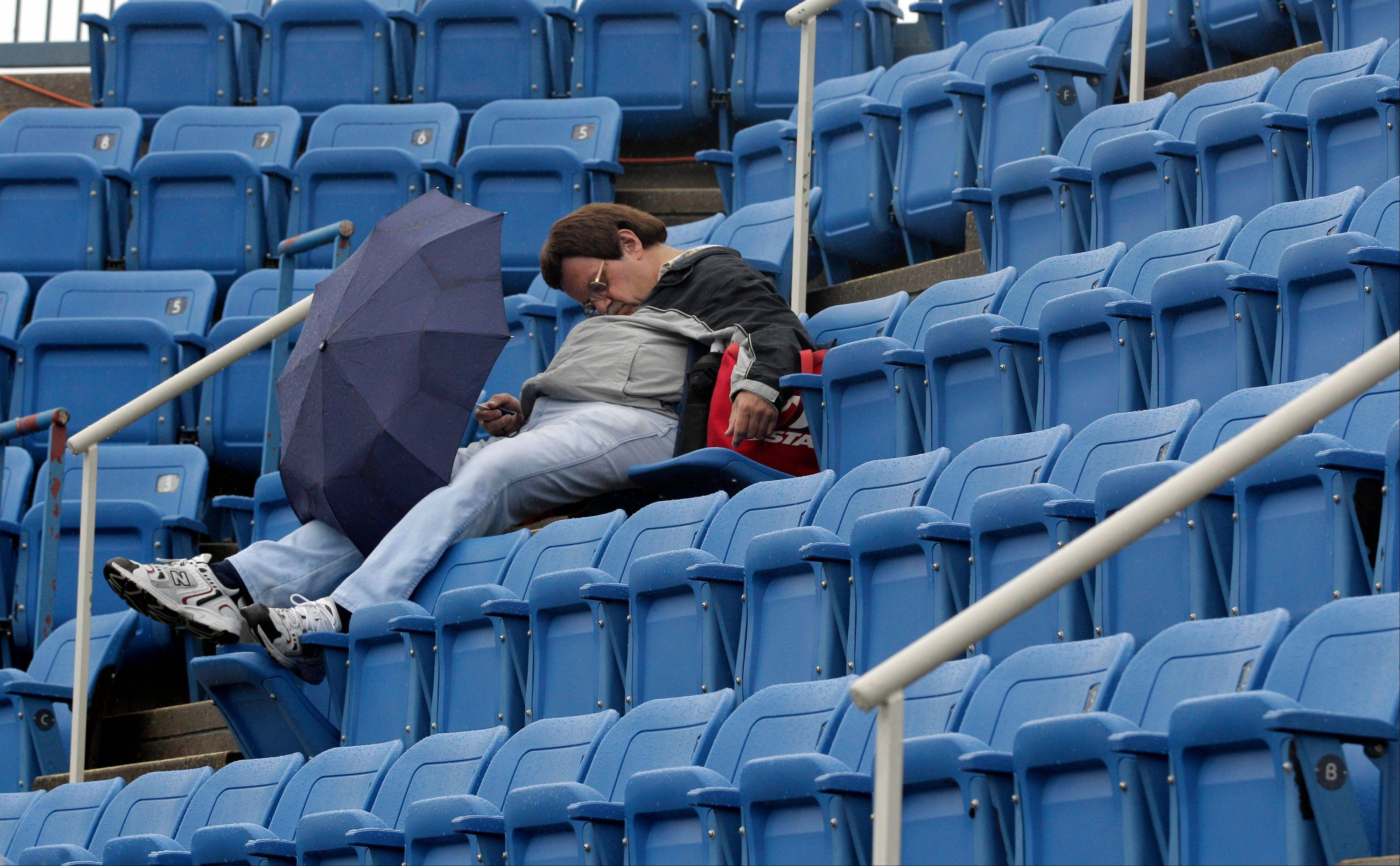 A tennis patron falls asleep in the stands during a rain delay Wednesday at the U.S. Open tennis tournament in New York.