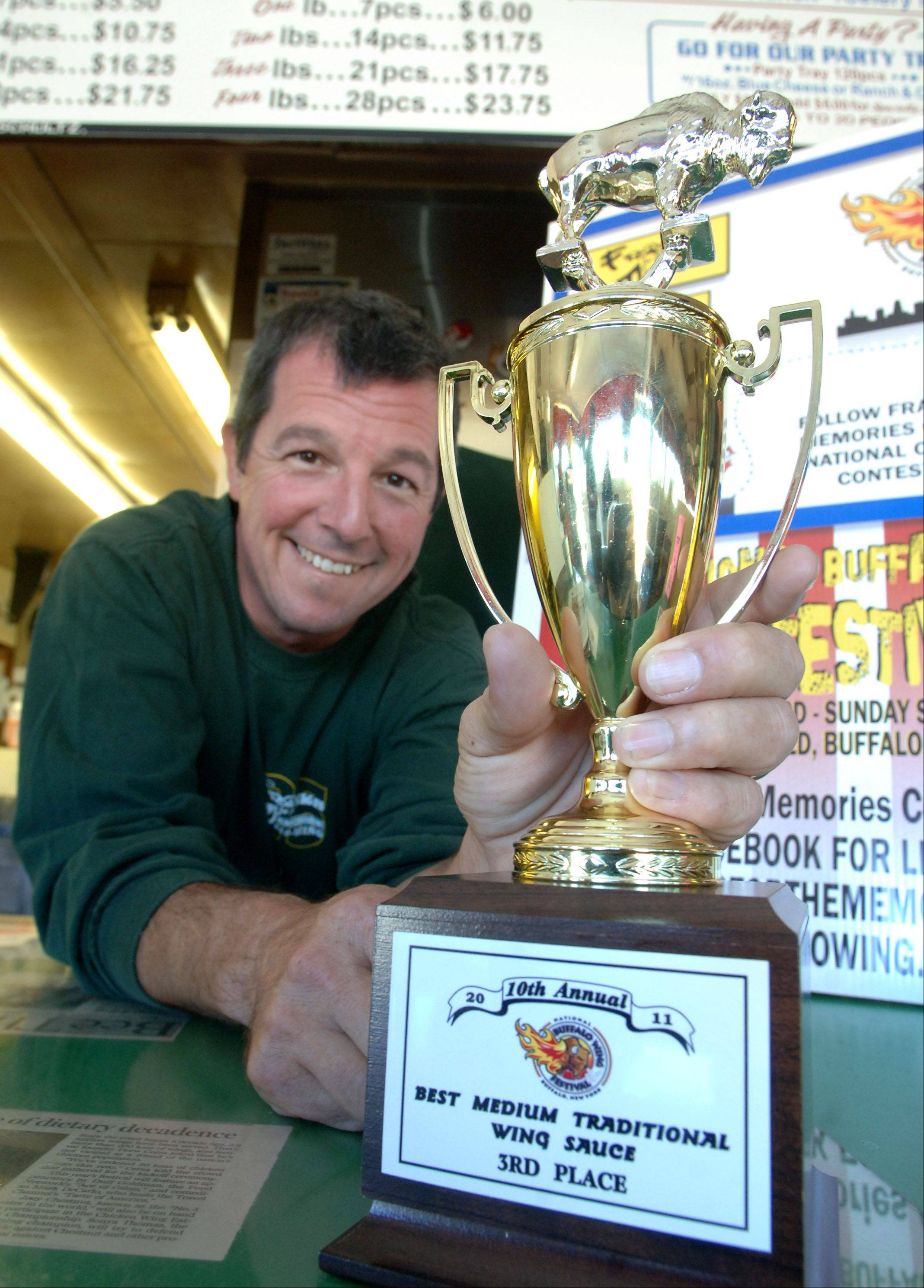 Jim Schultz Jr., owner of Franks for the Memories in Mundelein, with his third place trophy in the Best Medium Traditional Wing Sauce category from the national Buffalo Wing Festival in New York.