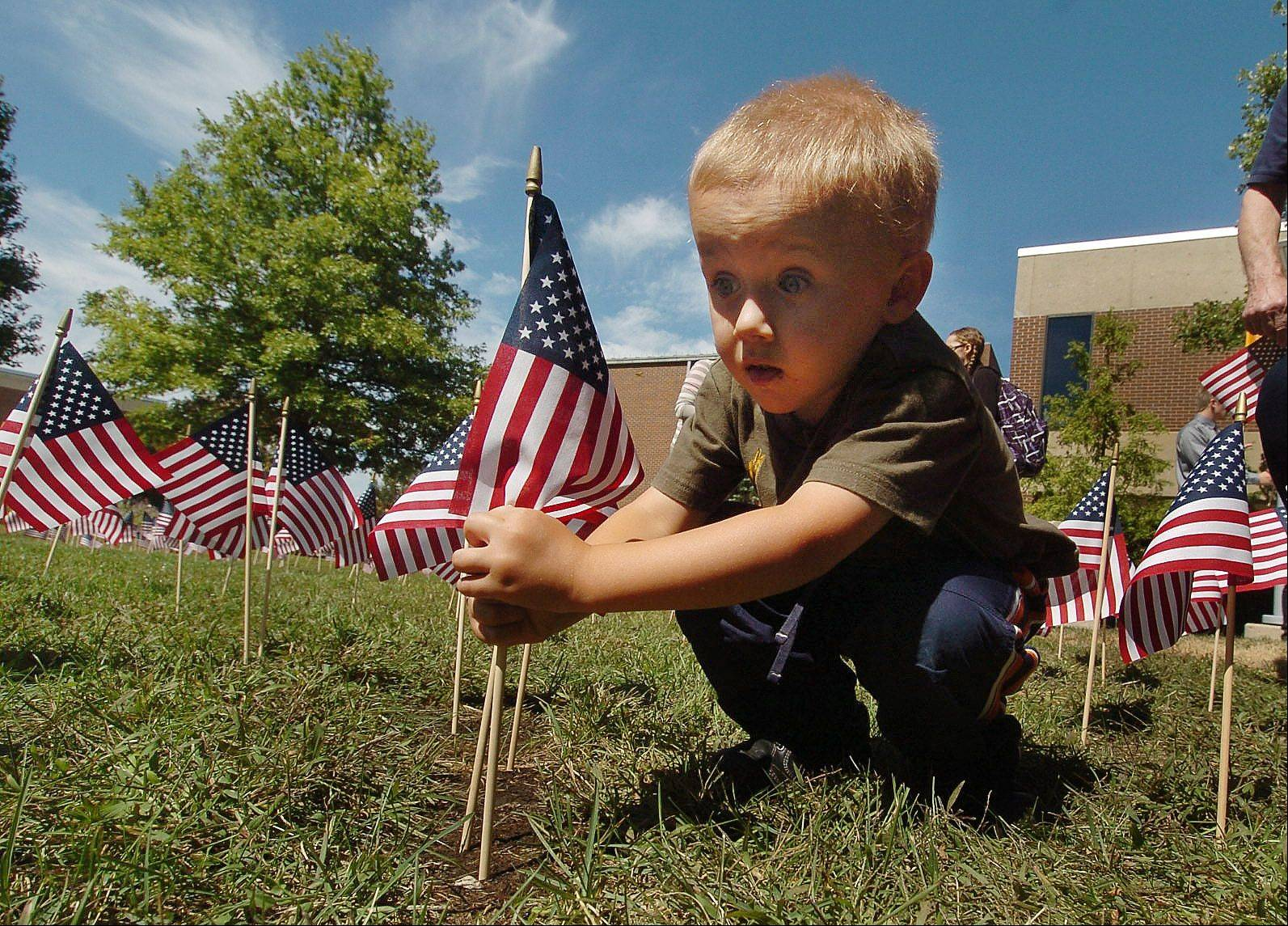 Jack Daly, 4, plants a flag at the Harper College observance on Thursday.