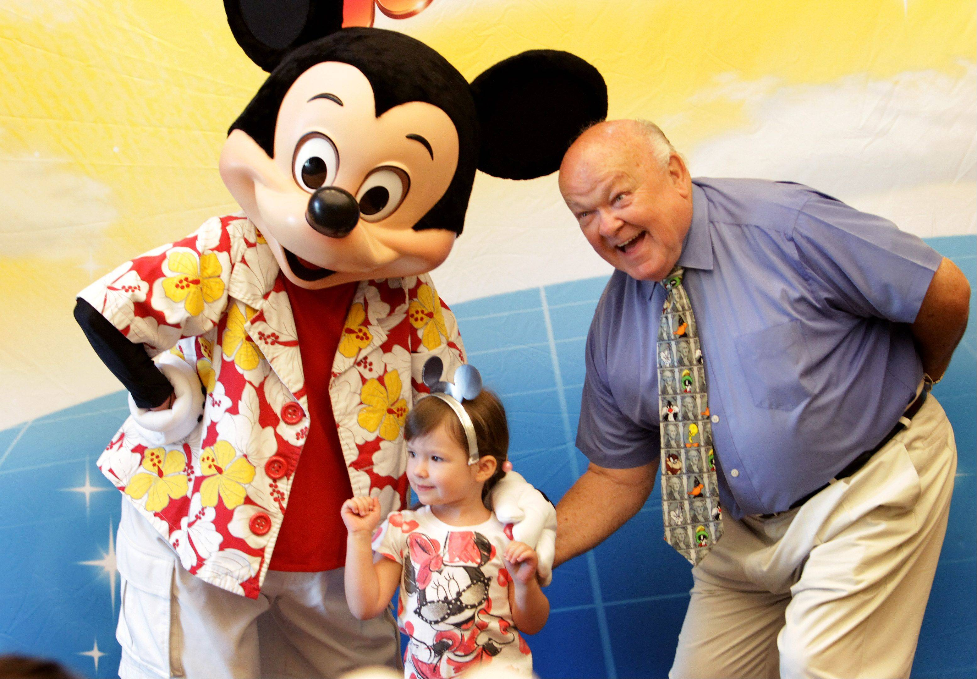 "Mickey Mouse and Naperville Mayor George Pradel pose with Rionnah O'Connor, 3, at the 95th Street Library in Naperville. Mickey made a surprise appearance Thursday for the kids while on a break from ""Disney On Ice presents Mickey & Minnie's Magical Journey"" at the United Center."