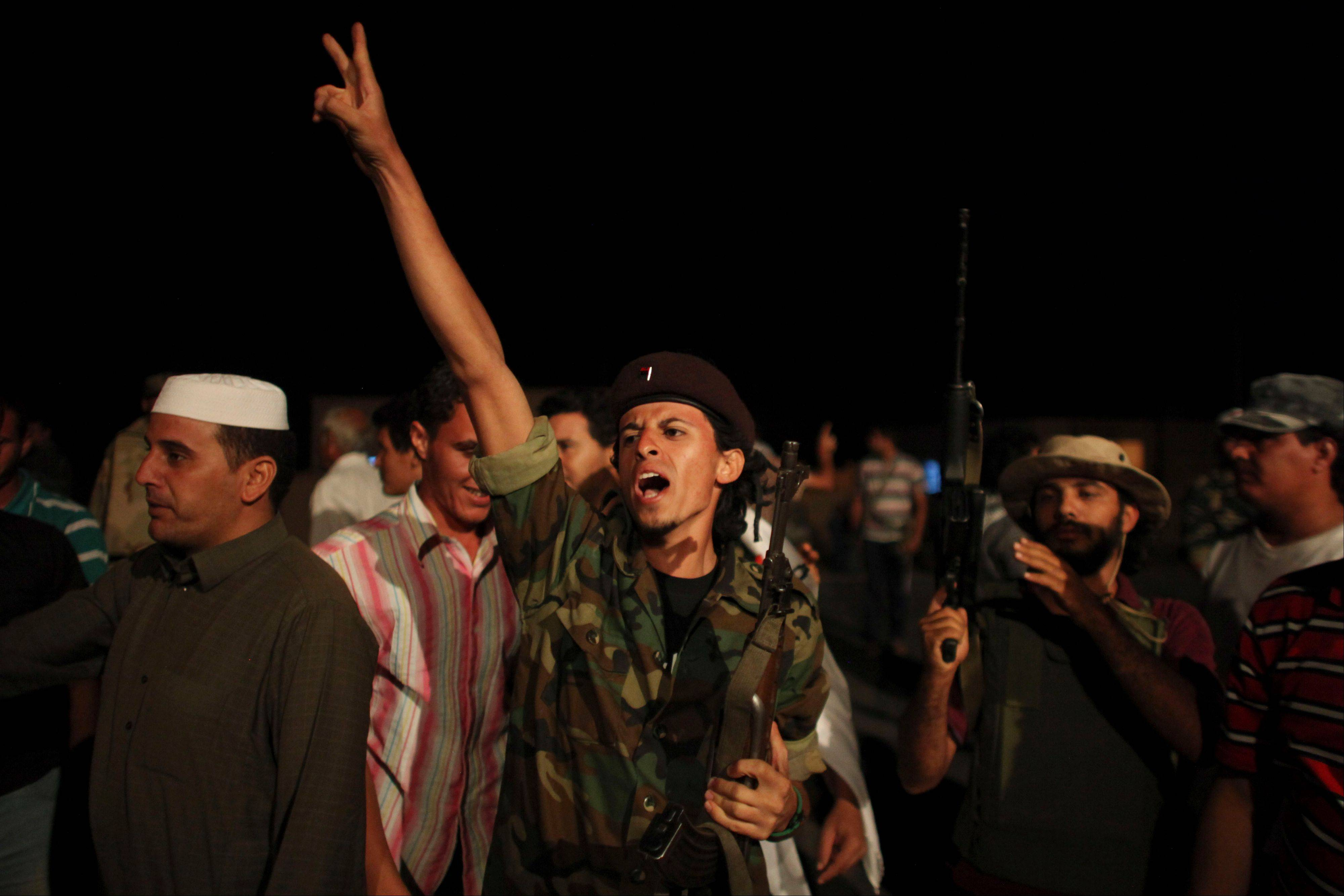 Former rebel soldier, Mootaz Isse, 25, electronics student, center, celebrates as other rebel soldiers leave to the front, at a checkpoint between Tarhouna and Bani Walid, Libya. Associated Press