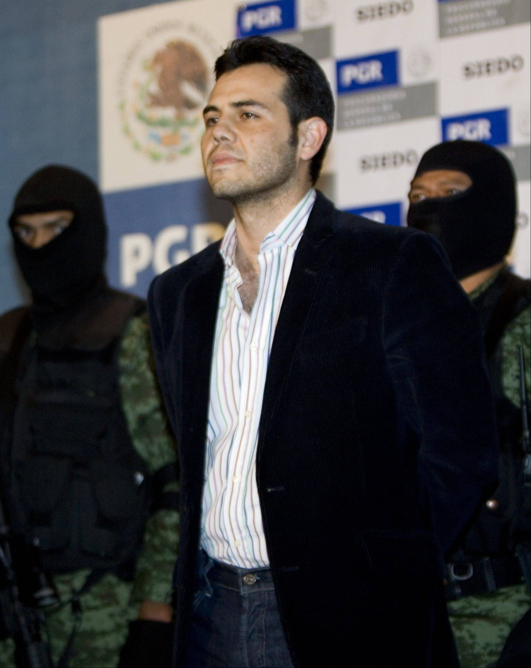 Military officers escort drug trafficker Vicente Zambada during his presentation to the media in Mexico City. Zambada is the son of Mexican drug lord Ismael Zambada, head of the Sinaloa cartel.
