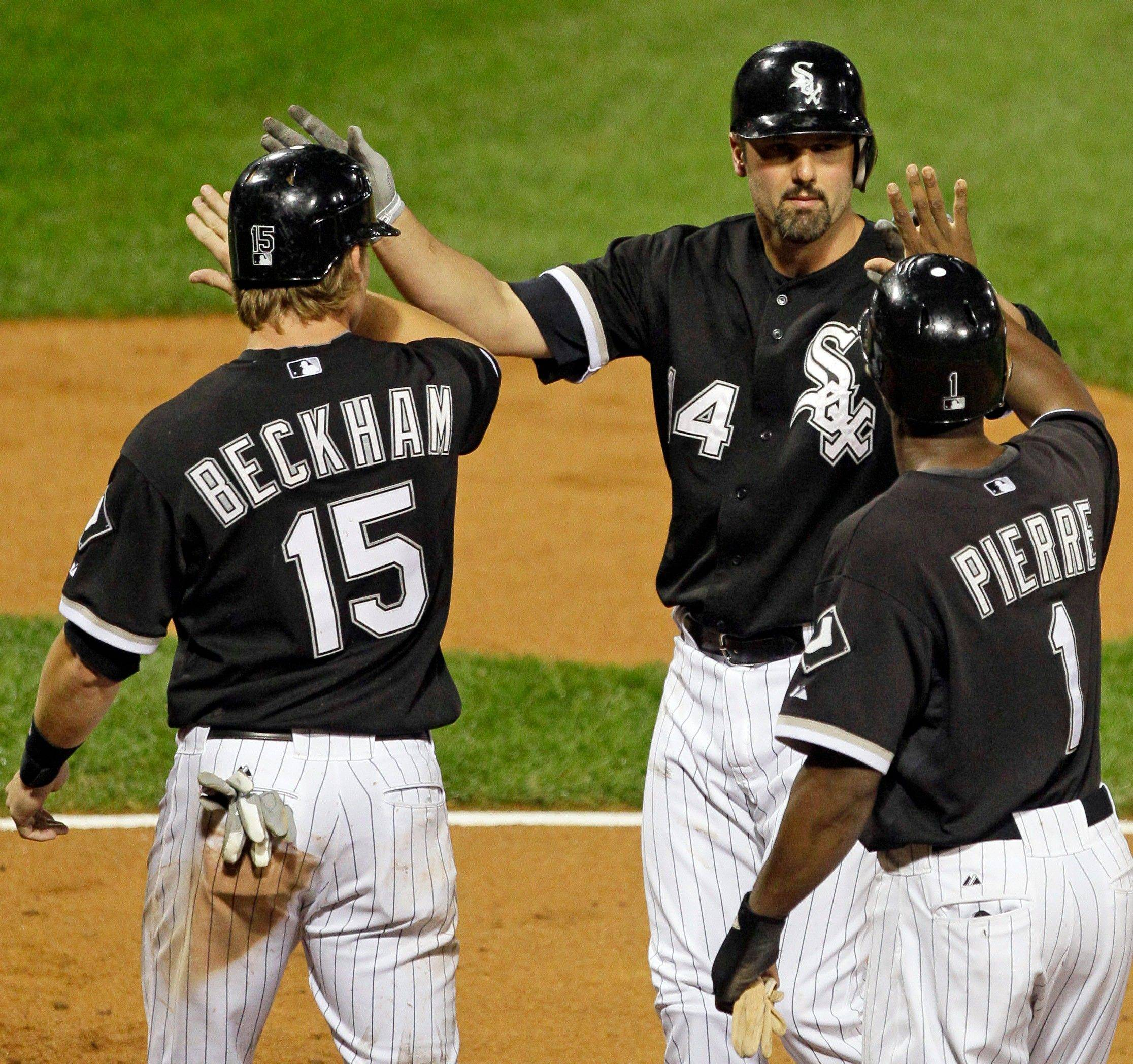 Paul Konerko, middle, celebrates with Gordon Beckham (15) and Juan Pierre (1) after hitting a grand slam during the White Sox' 7-run seventh inning.