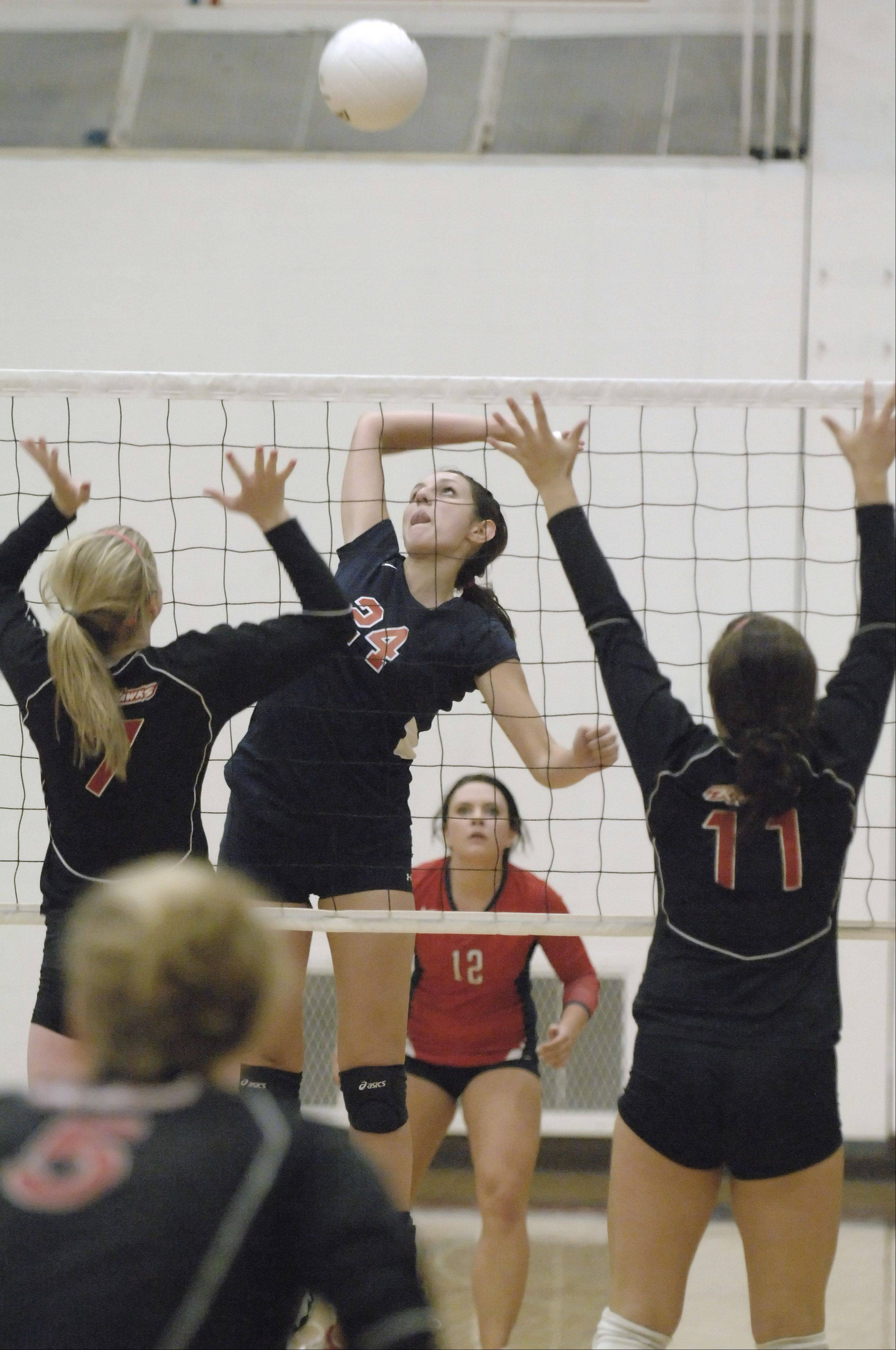 West Aurora's Lauren Wilson winds up for a spike over to Naperville Central's Nikki Connors and Maddie Slambekos in the first game on Thursday, September 8.