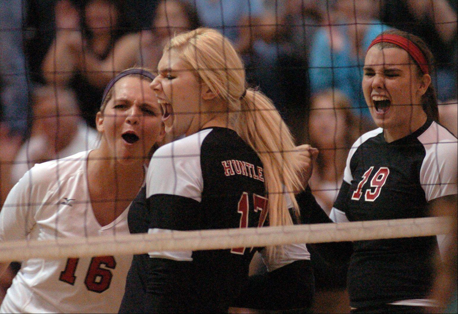 Huntley's Amy Dion, left, Jaina Jackson and Ashley Smith celebrate after gaining a point against Crystal Lake South Thursday night.
