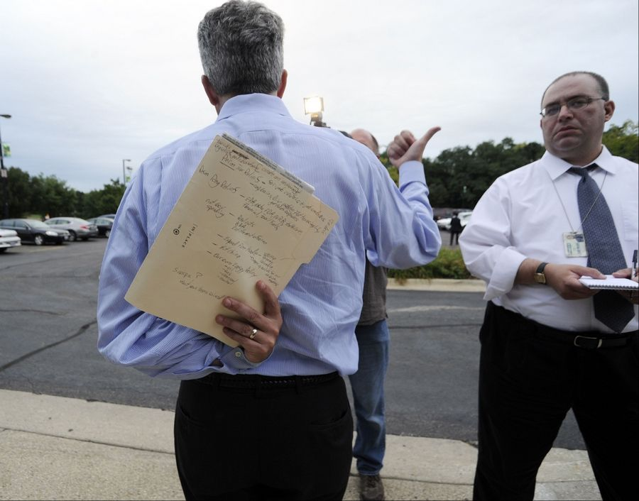 U.S. Rep. Joe Walsh talks to the media while holding his notes for the small business forum behind his back at the Schaumburg Prairie Center for the Arts on Thursday.
