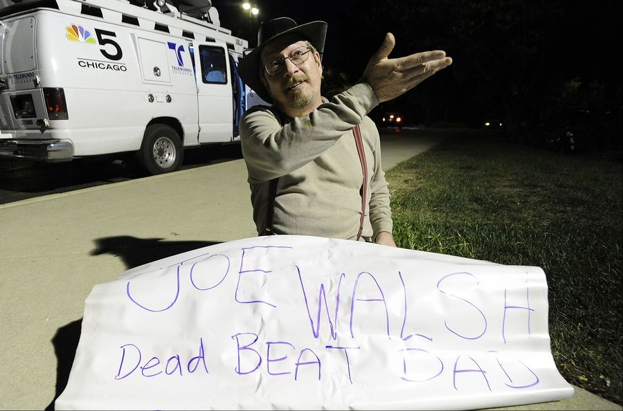 Schaumburg's Tony Domino sits outside Schaumburg's Prairie Center for the Arts with his protest sign and waits for U.S. Rep. Joe Walsh to exit from the business forum held on Thursday night.