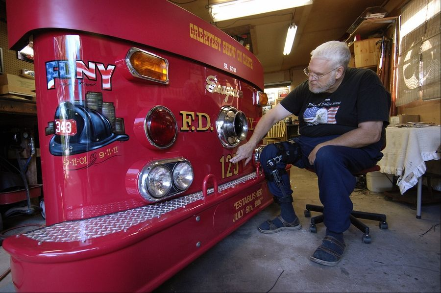 Elgin firefighter John Tobin works on a refurbished front of a 1981 fire truck that he is taking to New York to give to firefighters he met while helping dig through the rubble of the World Trade Center. They will display it in their station house.
