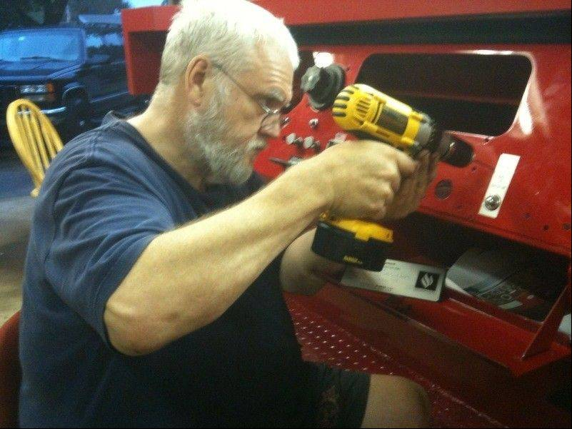 Elgin firefighter John Tobin works in his garage to restore the old fire truck's lights and siren. The finished project is a gift for the New York Fire Department.