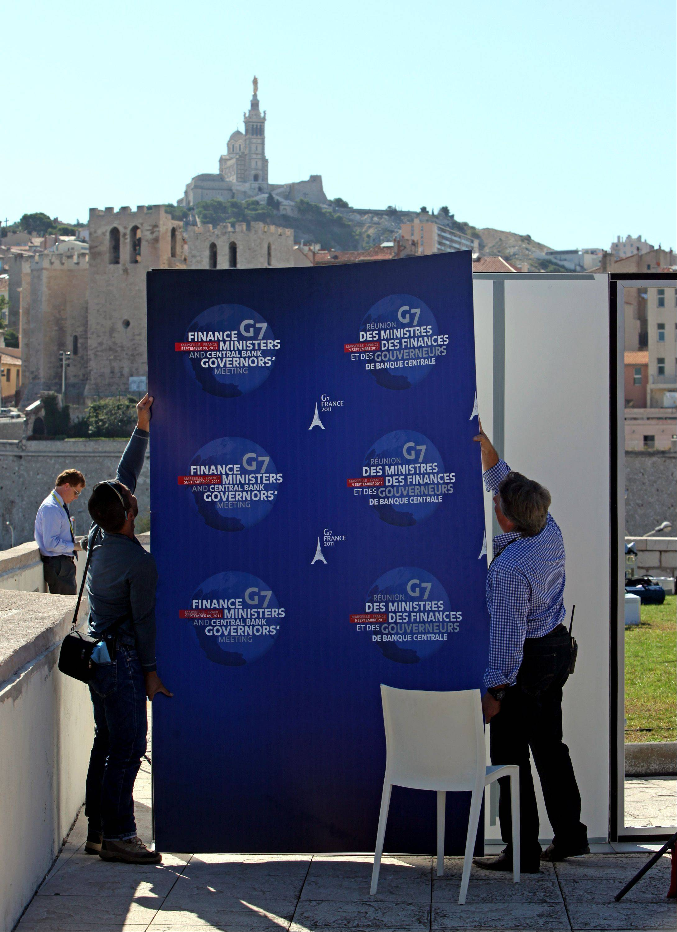 Employees install a G7 summit poster near the Le Palais du Pharo, the location for the G7 finance ministers and central bank governors meeting in Marseille, France, on Friday, Sept. 9, 2011. The Group of Seven, the United States, France, Germany, Italy, Britain, Japan and Canada meet in the French port of Marseilles today for the two day meeting.