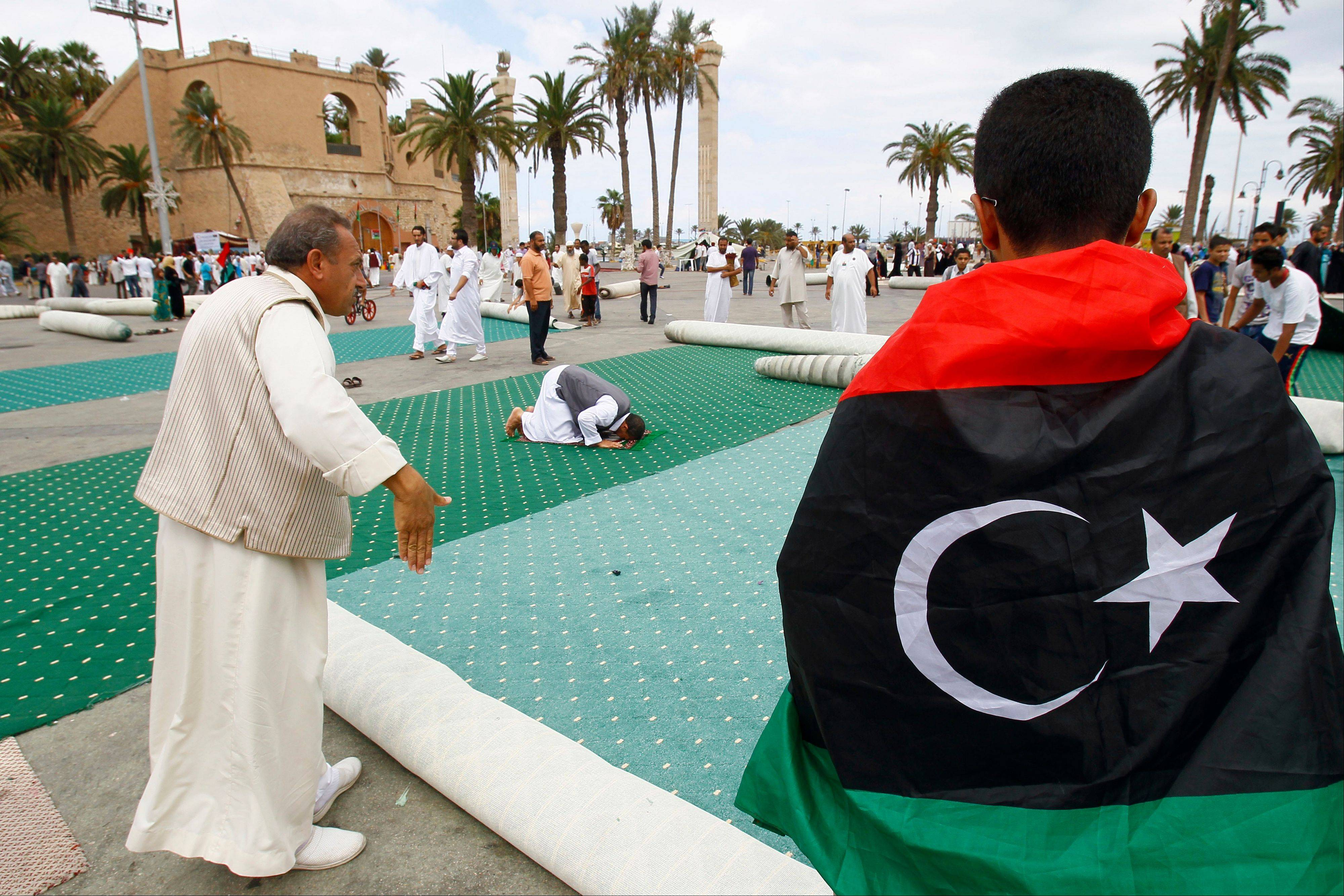 A Libyan man gestures as he arrives late for prayer as revolutionaries and residents of Tripoli roll up the carpet after the weekly Muslim Friday prayers at the former Green Square, renamed Martyrs Square, in Tripoli, Libya.