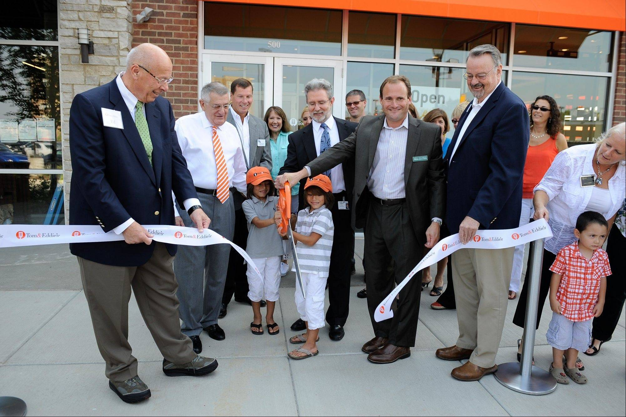 Taylor Riggi, 6, left, and his twin brother, Tyler, cut the ribbon with Tom & Eddie�s co-founders Tom Dentice and Ed Rensi at the grand opening of Tom & Eddie�s new location in Vernon Hills.