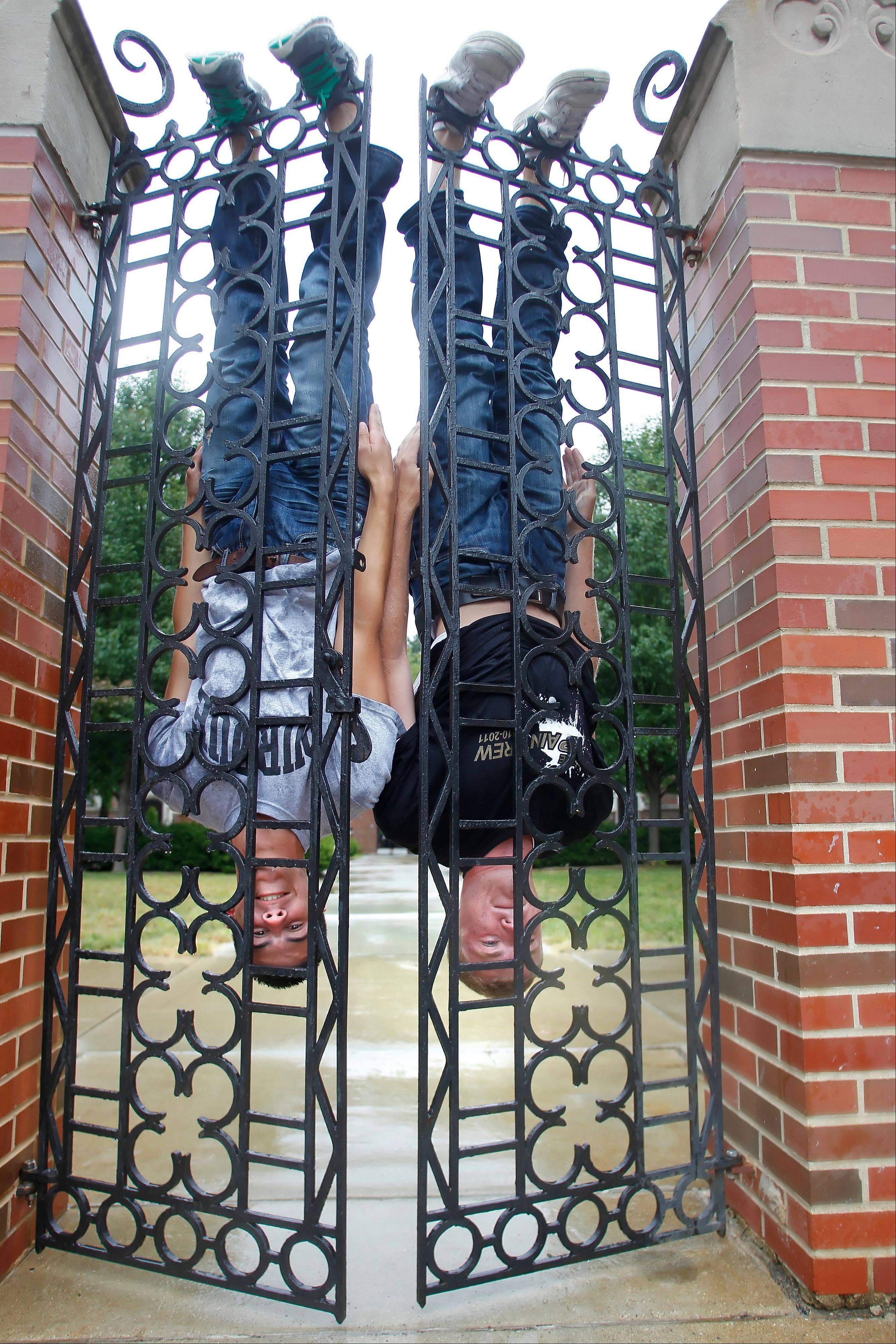 "Ben Lins, left, and Chris Ganz hang upside down on wrought iron gates Thursday at Windsor Hall on the campus of Purdue University in West Lafayette, Ind. The two men along with fellow freshmen Ryan Herberger and Chandler Welsh began what they call ""Batmanning"" shortly after arriving on campus."