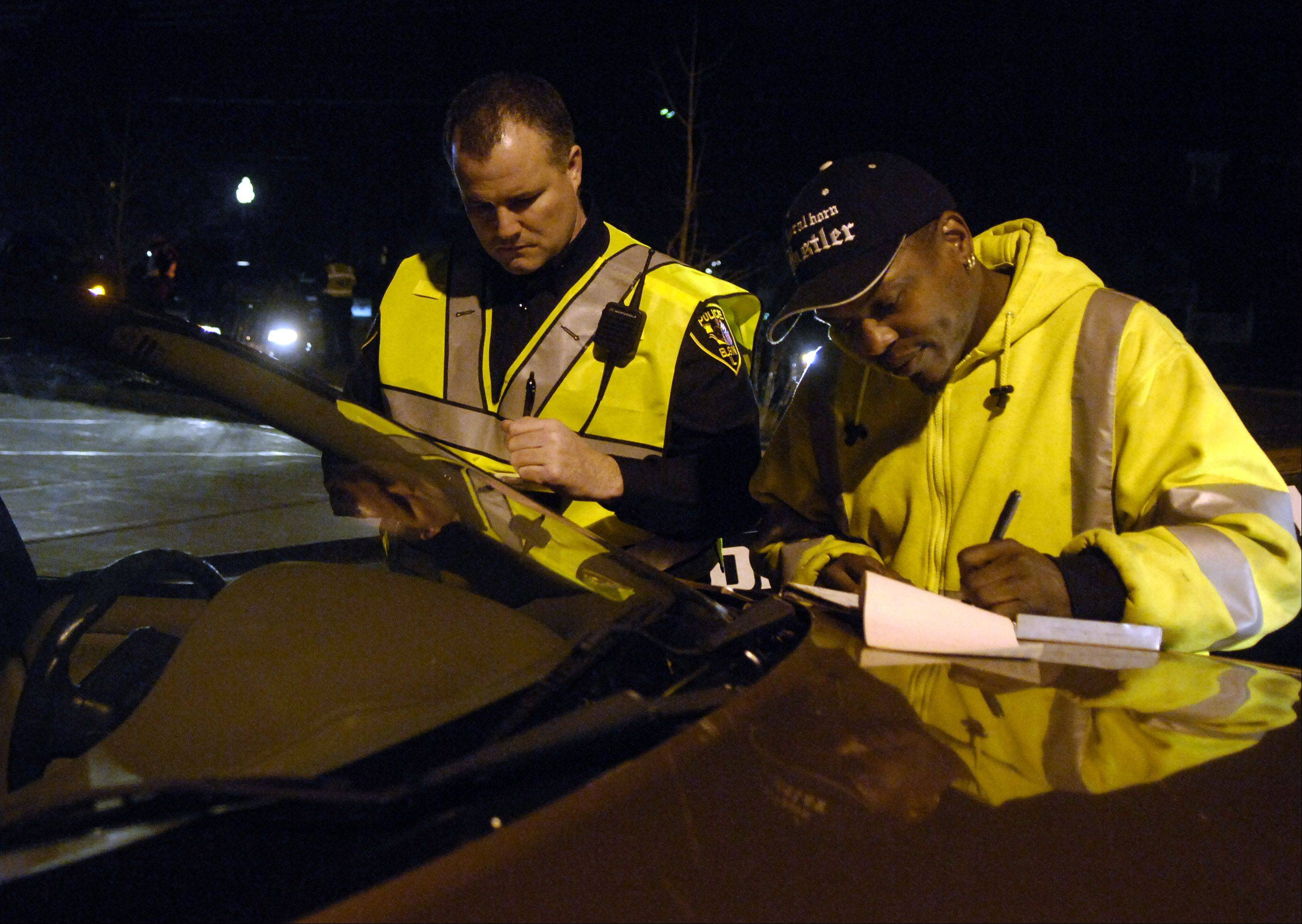 Elgin Police Lt. Sean Rafferty and Artie's Towing driver Derrick Gholston finish paperwork before hauling away a car at a safety checkpoint at the U-46 administration building on East Chicago Street.