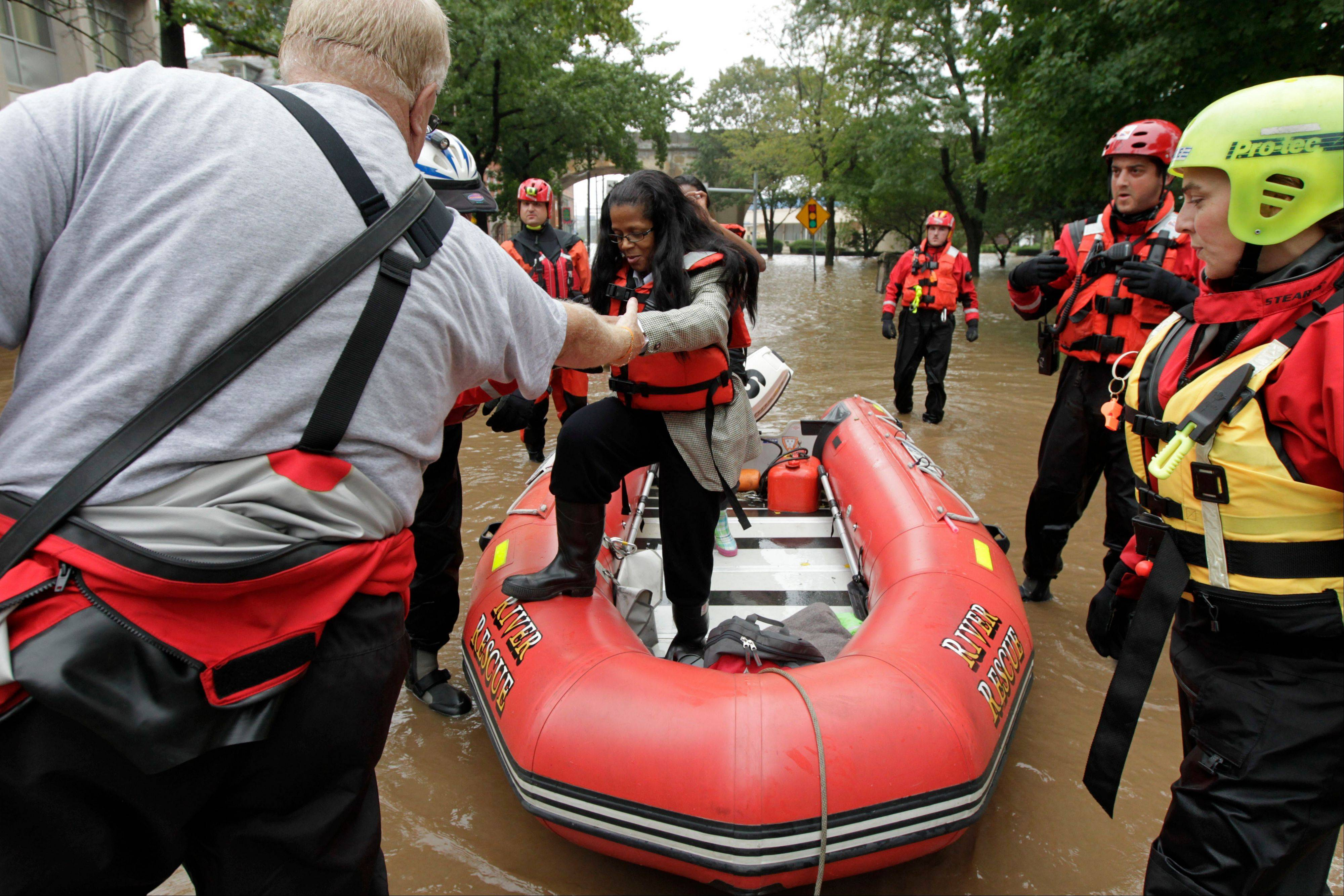 Members of the Harrisburg River Rescue help Mayor Linda Thompson out of the boat after going to the flooded Shipoke area during flooding caused by rainfall from the remnants of Tropical Storm Lee in Harrisburg, Pa.