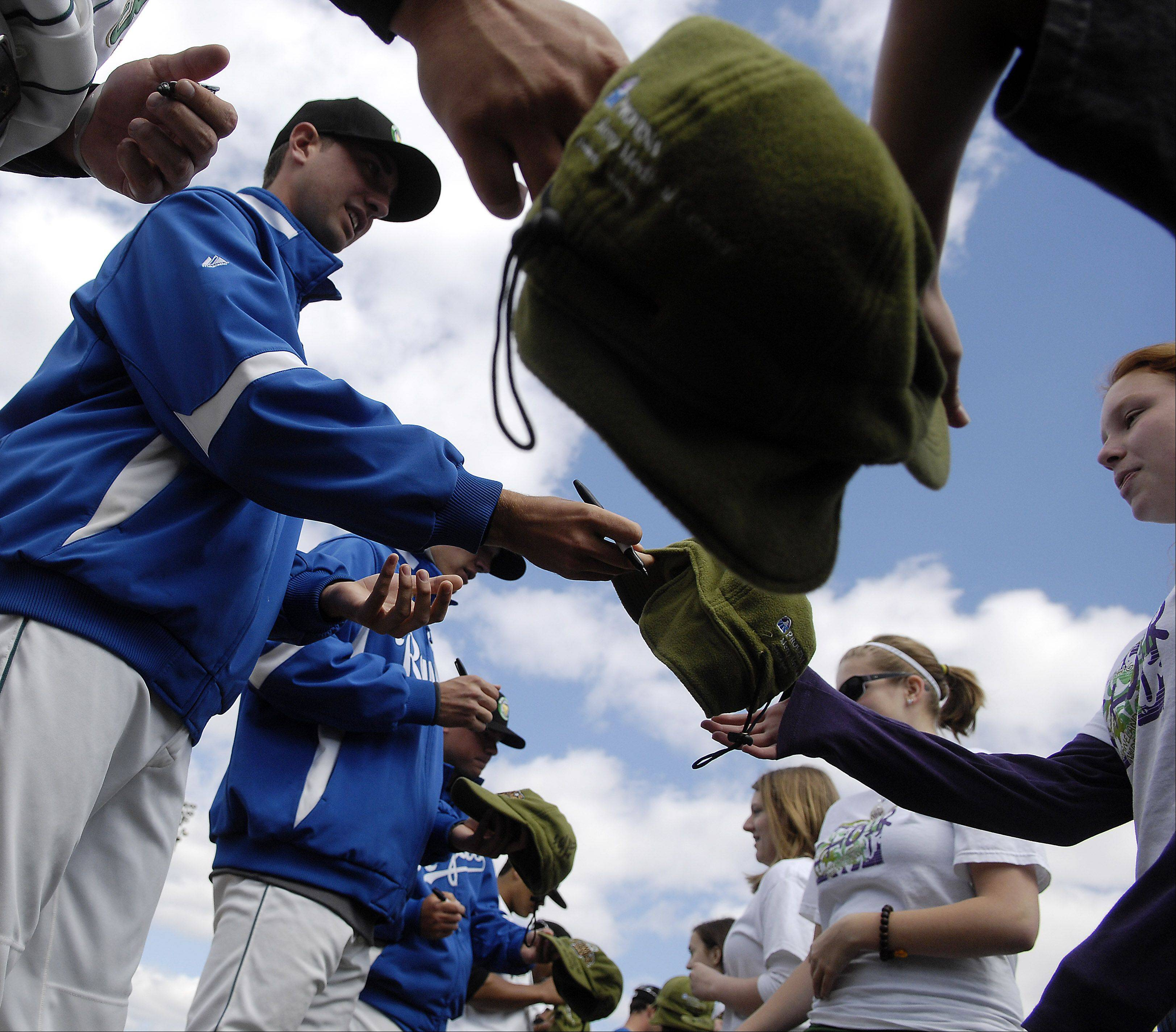 Players sign autographs before this year's home opener at Elfstrom Stadium in Geneva.