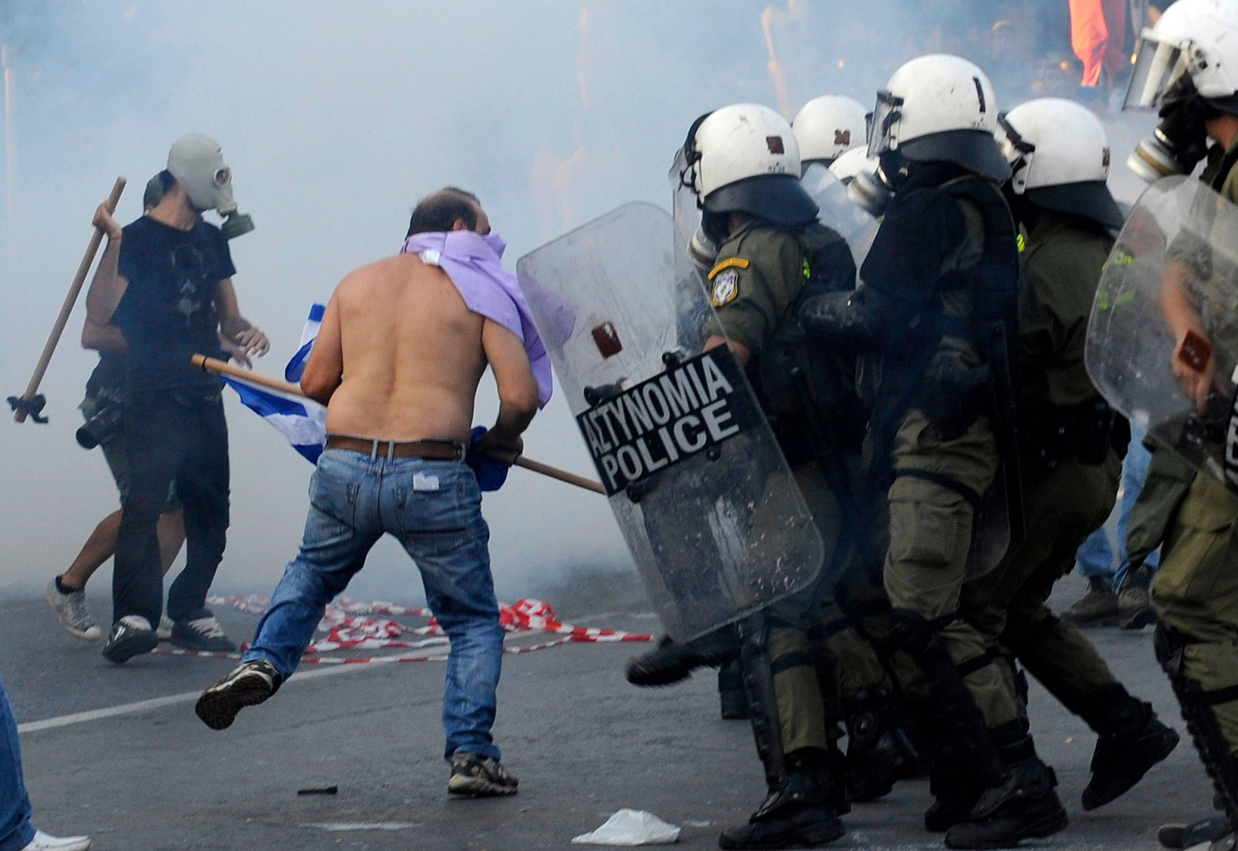 Protesting taxi drivers confront riot police Saturday during a demonstration in Thessaloniki, Greece.