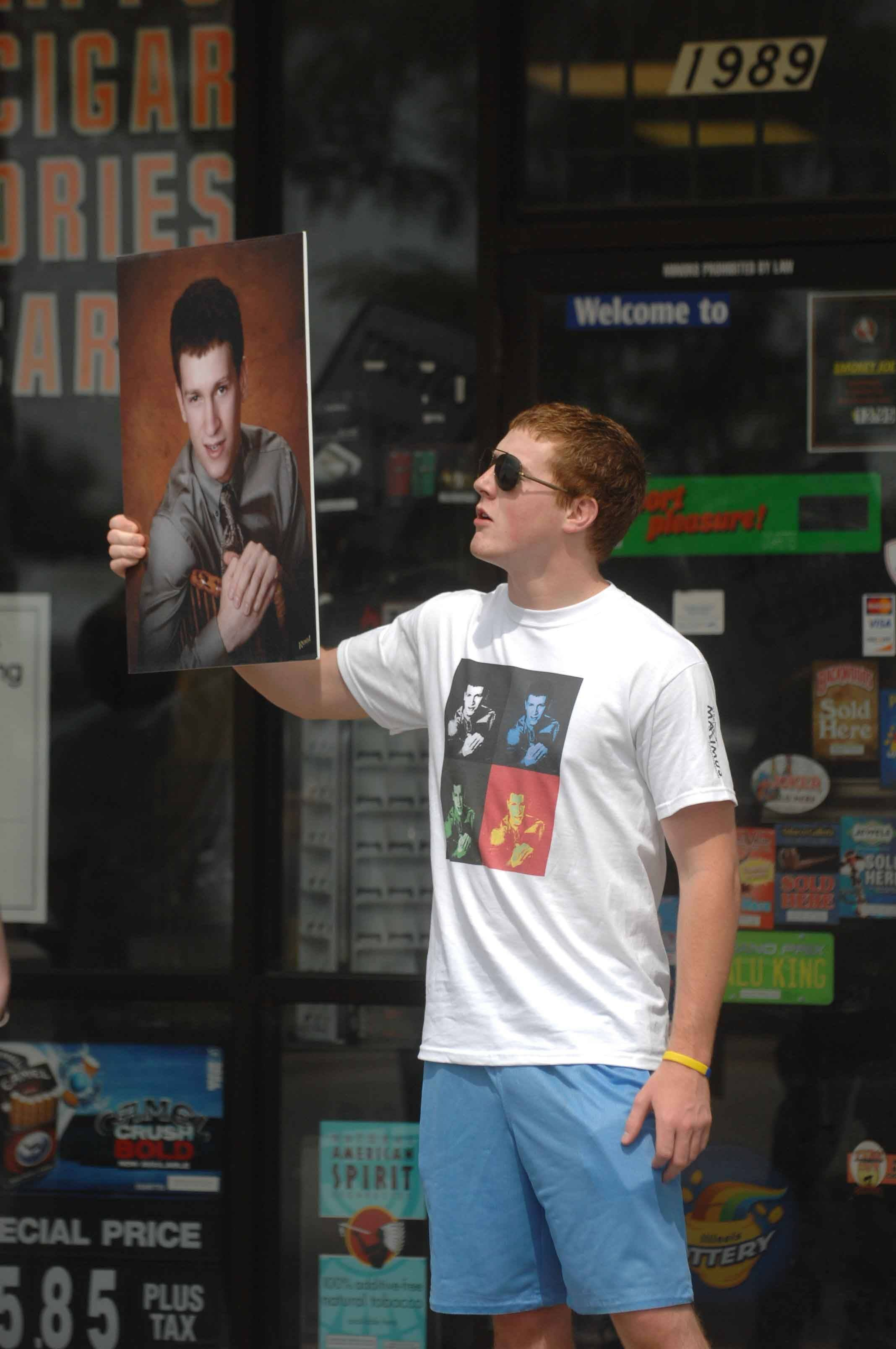 Sam McKinney holds a photo of his friend, Max Dobner, who died after smoking fake cannabis. McKinney was protesting at Aurora smoke shop Saturday.