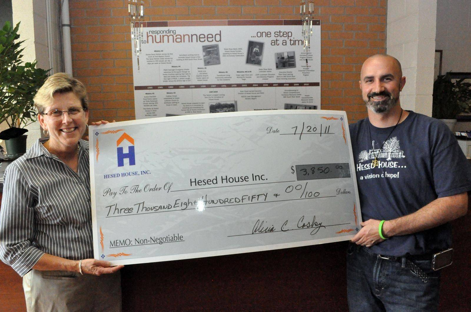Aurora University professor Alicia Cosky, left, presents the proceeds of the �Tee Off for Hesed House� student-run golf benefit to Ryan Dowd, executive director of the homeless shelter in Aurora.