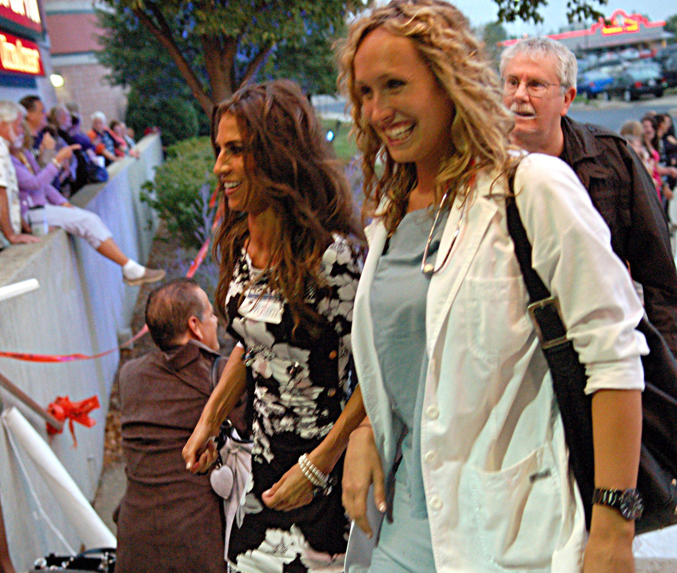 Natalie Simpson of Huntley, left, and Elizabeth Steffen of Crystal Lake walked up the white carpet Friday during the movie premiere for �Contagion� at Elgin Marcus Fox Theatre. Both were extras during filming at Sherman Hospital in Elgin.
