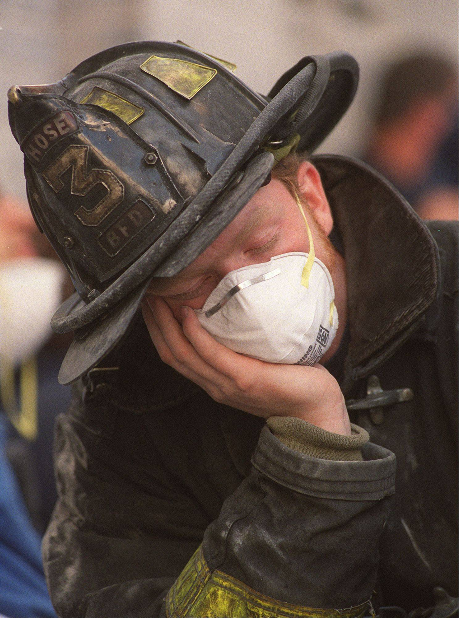 Bill Fennelly, a volunteer firefighter from Baldwin, N.Y., pauses for a moment at the World Trade Center collapse in New York, Thursday morning, Sept. 13, 2001.