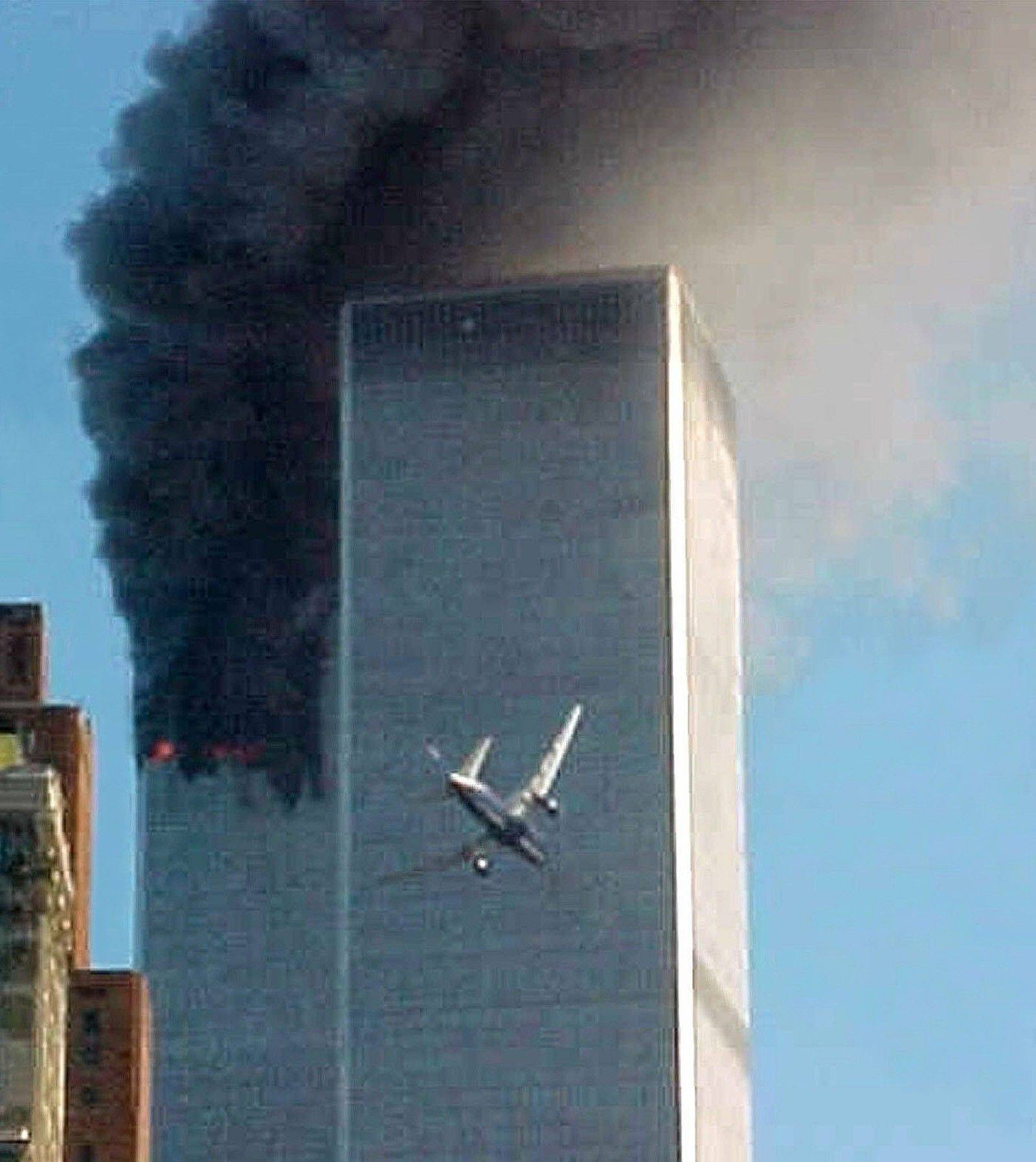 United Airlines Flight 175 approaches the south tower of the World Trade Center in New York shortly before collision as smoke billows from the north tower on Sept. 11, 2001.