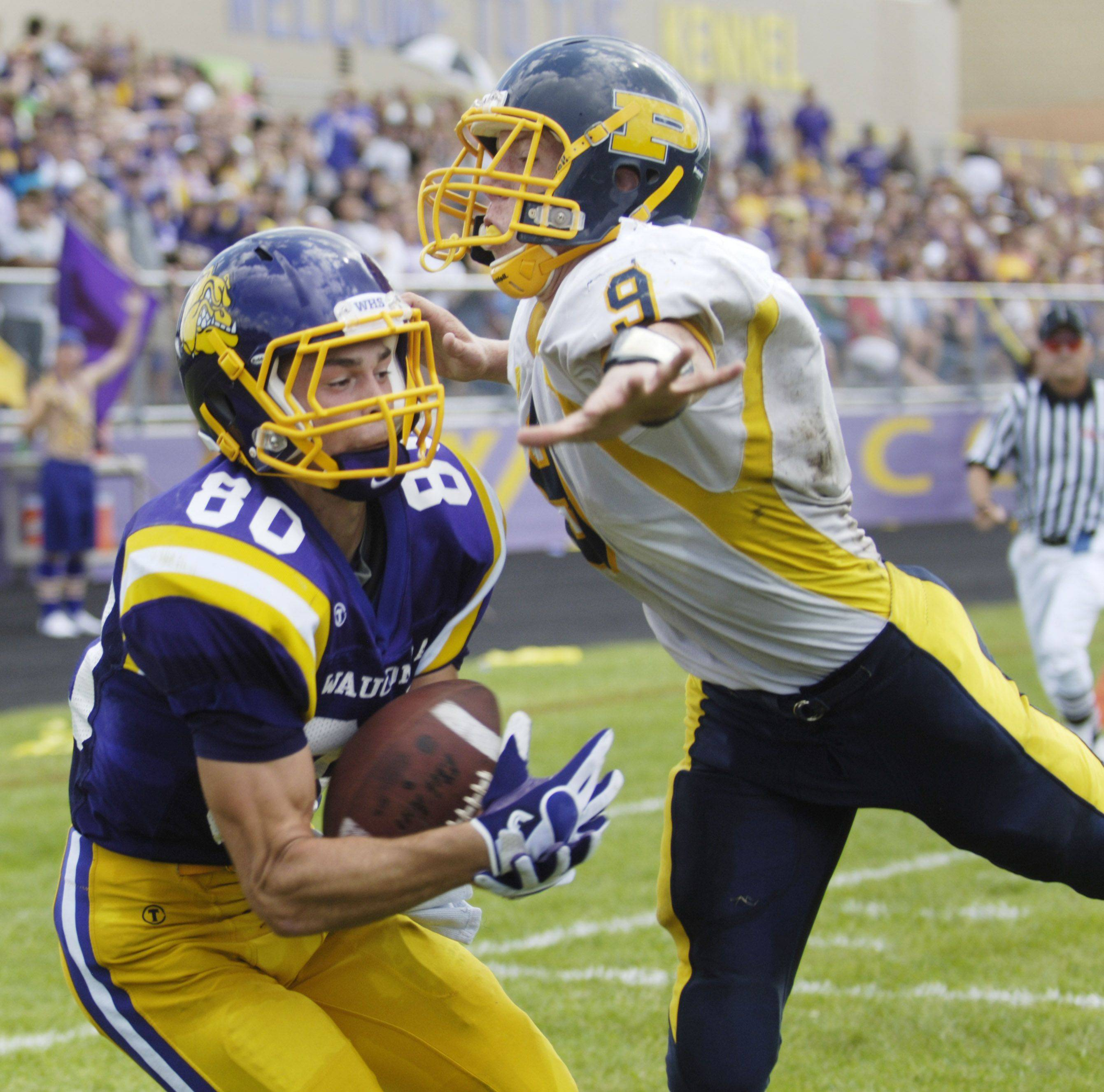 At left: Wauconda�s Jake Ziolkowski catches a touchdown pass in the end zone just past the outstretched hand of Round Lake�s Anthony Burton.