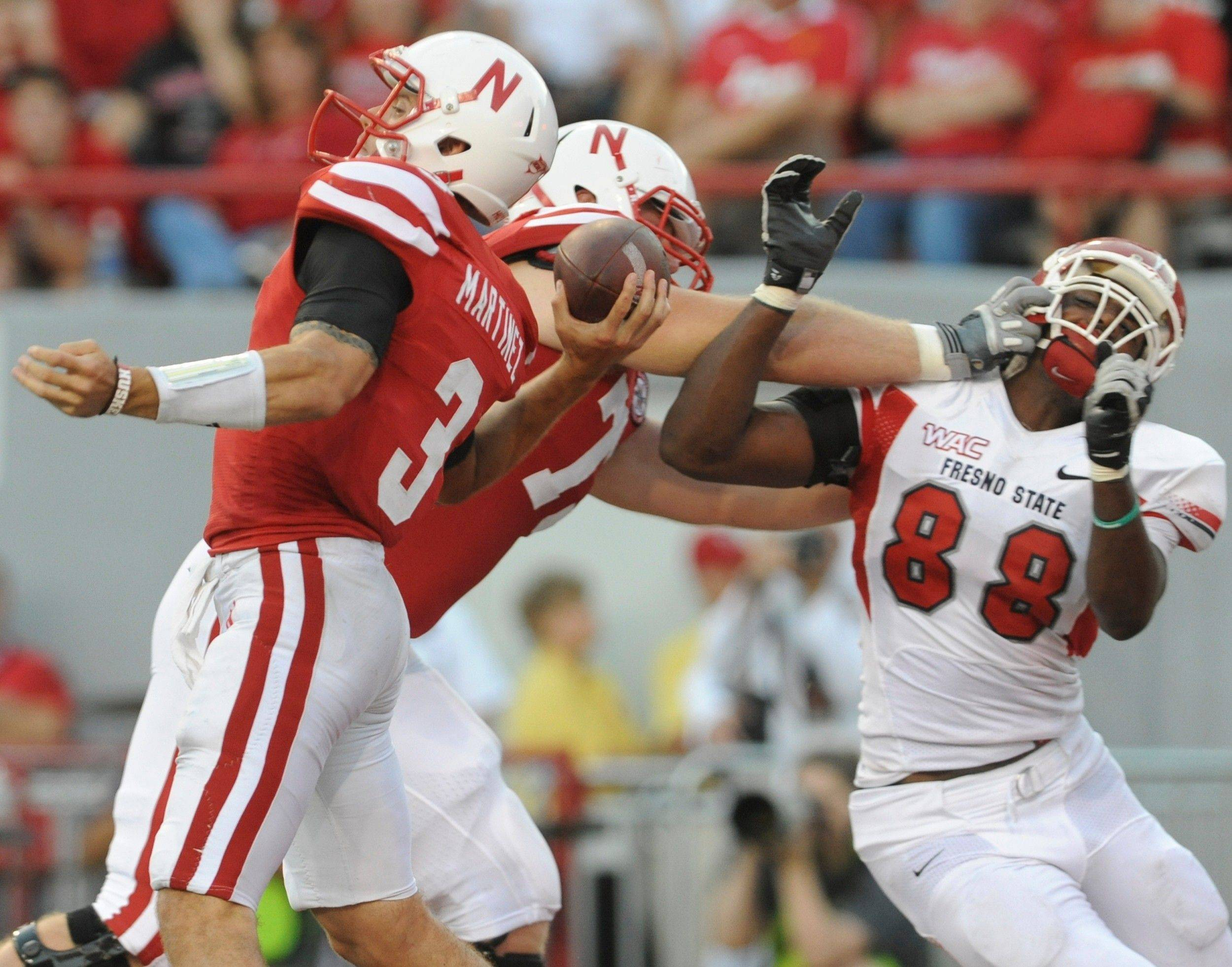 Nebraska�s Tyler Moore, center, protects quarterback Taylor Martinez (3) from Fresno State�s Tristan Okpalaugo (88) in the first half Saturday night.