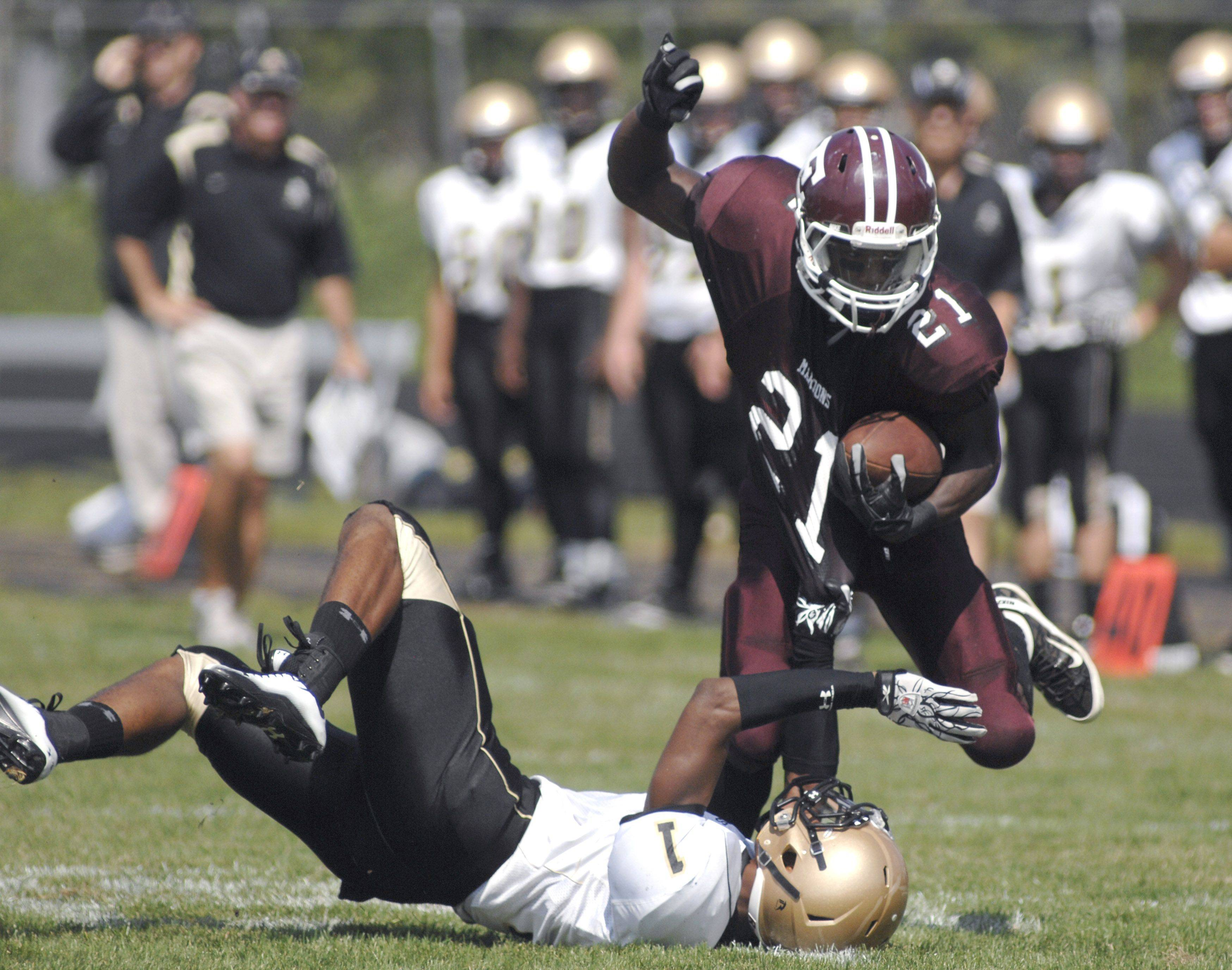Elgin�s Dennis Moore can�t be pulled down by Streamwood�s Blake Holder in the first quarter on Saturday, September 10.