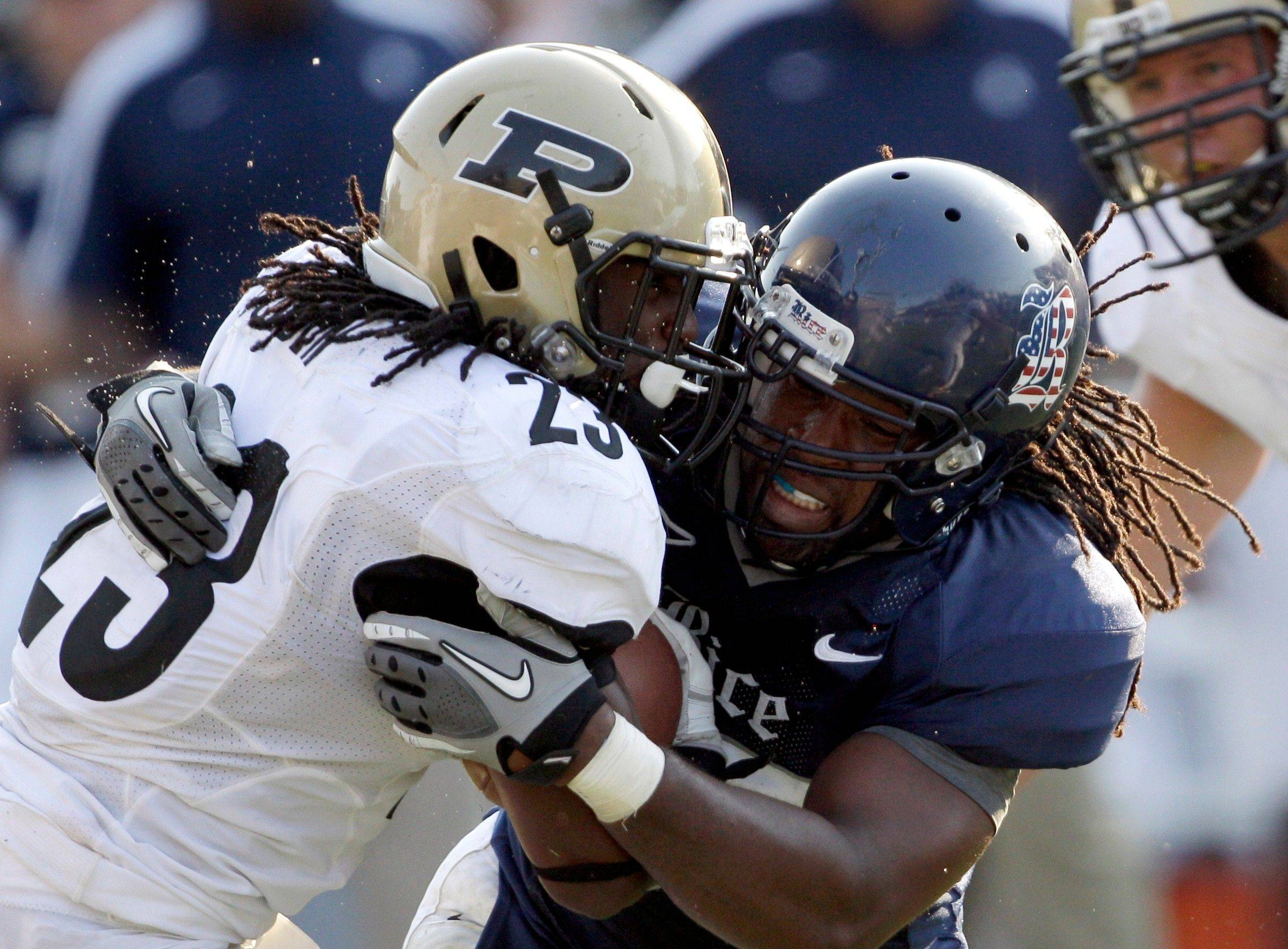 Purdue running back Ralph Bolden (23) is hit by Rice defensive end Jared Williams, right, during the fourth quarter Saturday. Rice won 24-22.