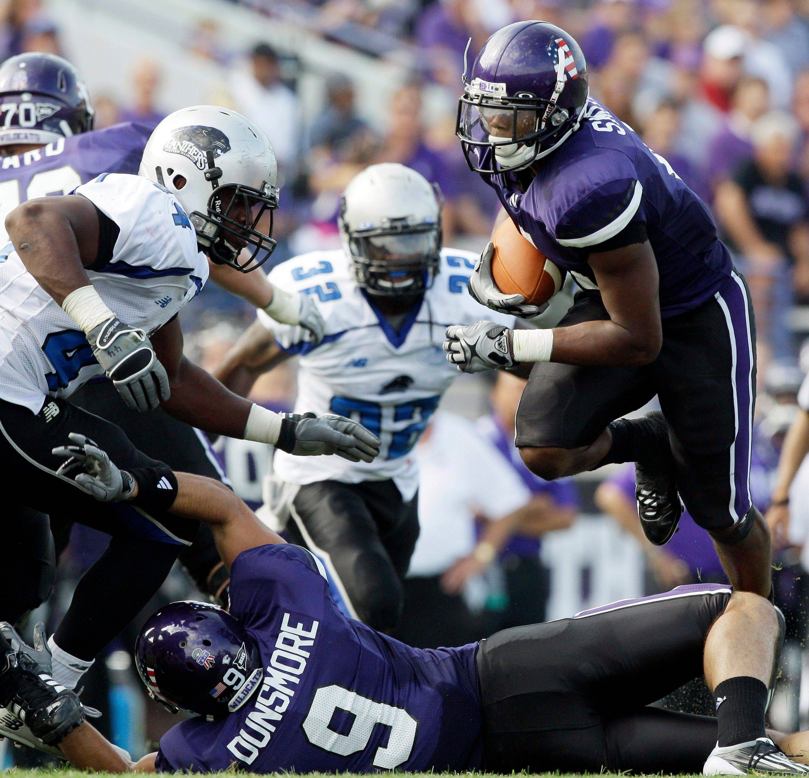 Northwestern running back Adonis Smith, right, leaps over tight end Drake Dunsmore (9) as Eastern Illinois defensive end Judes Amilcar (44), left, tries to tackle him during the second quarter Saturday.