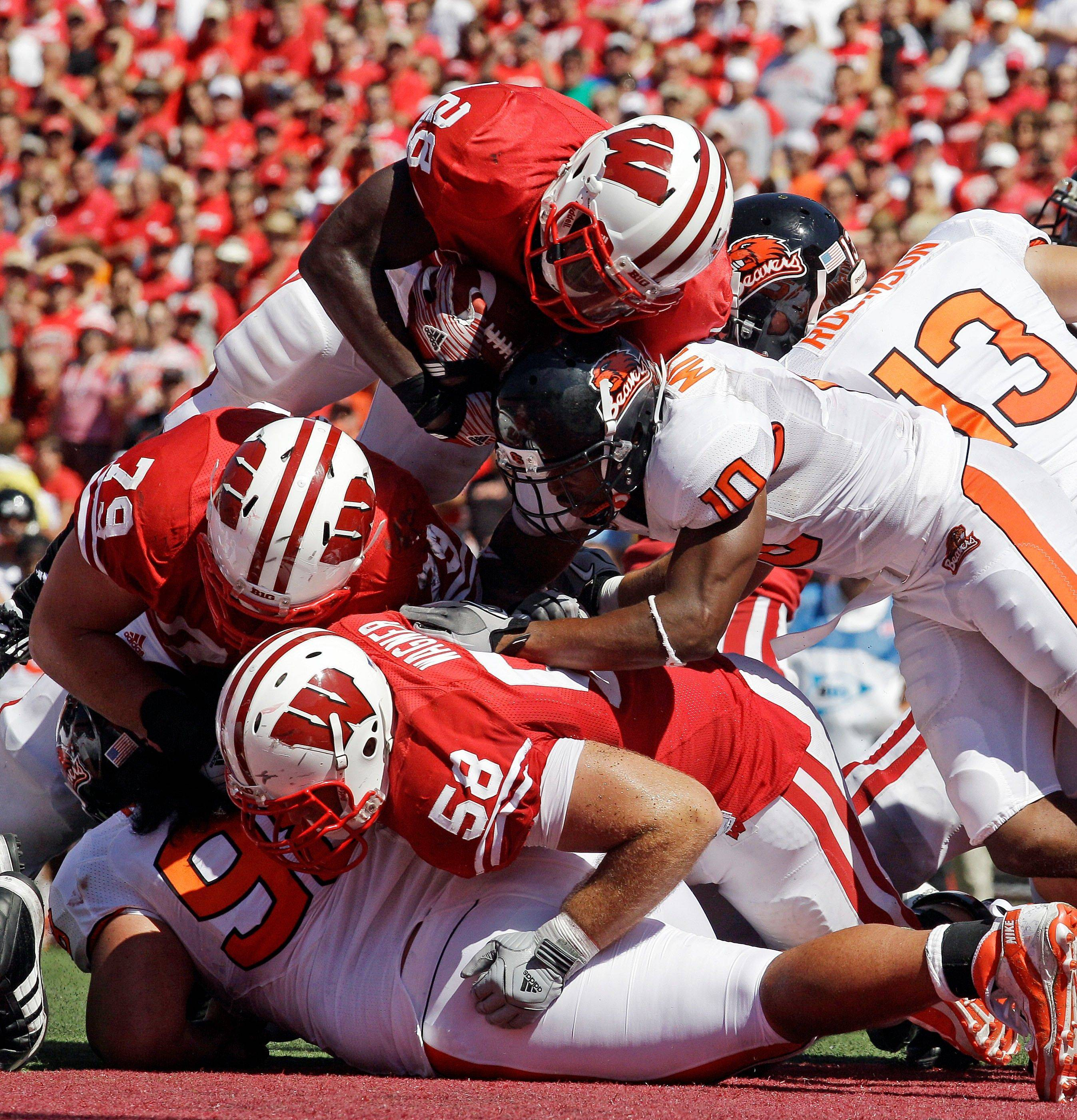 Wisconsin�s Montee Ball (28) leaps over teammates Ryan Groy (79), Ricky Wagner (58) and Oregon State�s Lance Mitchell (10) for a touchdown run during the second half Saturday. Wisconsin beat Oregon State 35-0.