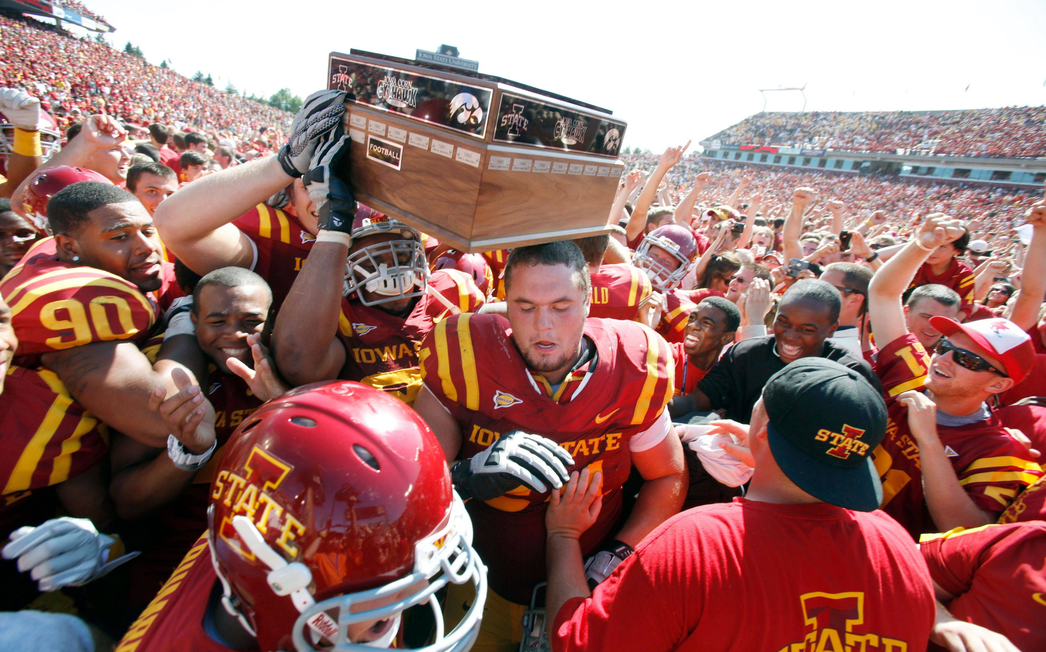 Iowa State players celebrate with fans after their 44-41 triple-overtime win over Iowa Saturday in Ames, Iowa.