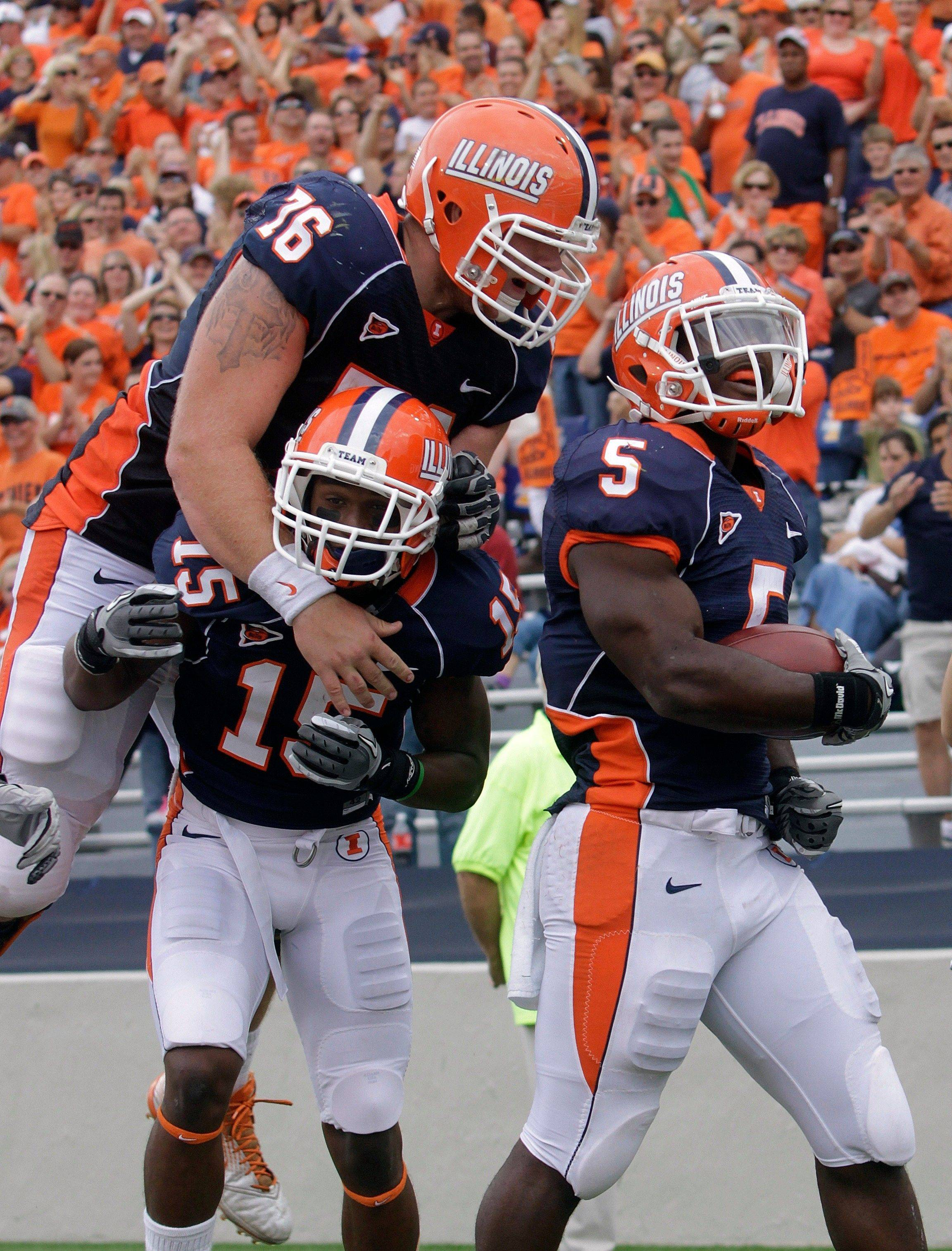 Illinois running back Donovonn Young (5) celebrates with offensive linesman Graham Pocic (76) and wide receiver Darius Millines (15) after Young scored a touchdown against South Dakota State in Champaignon Saturday. Illinois defeated South Dakota State 56-3.