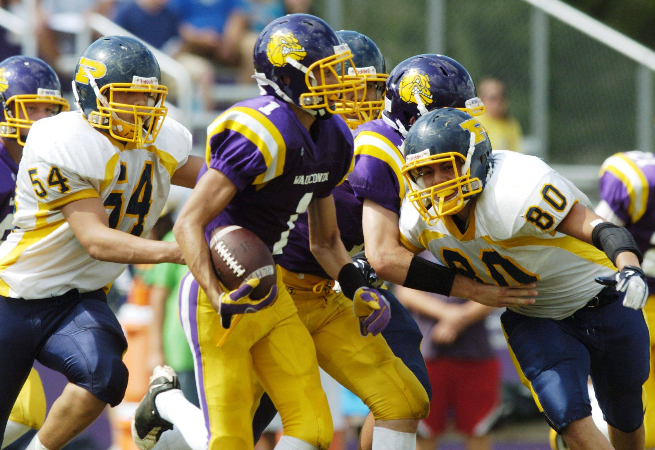 Wauconda's Eric Dragon, middle, carries the ball after making an interception as Round Lake's Luis Aceves, left, and Eddie Acevedo close in during Saturday's game.