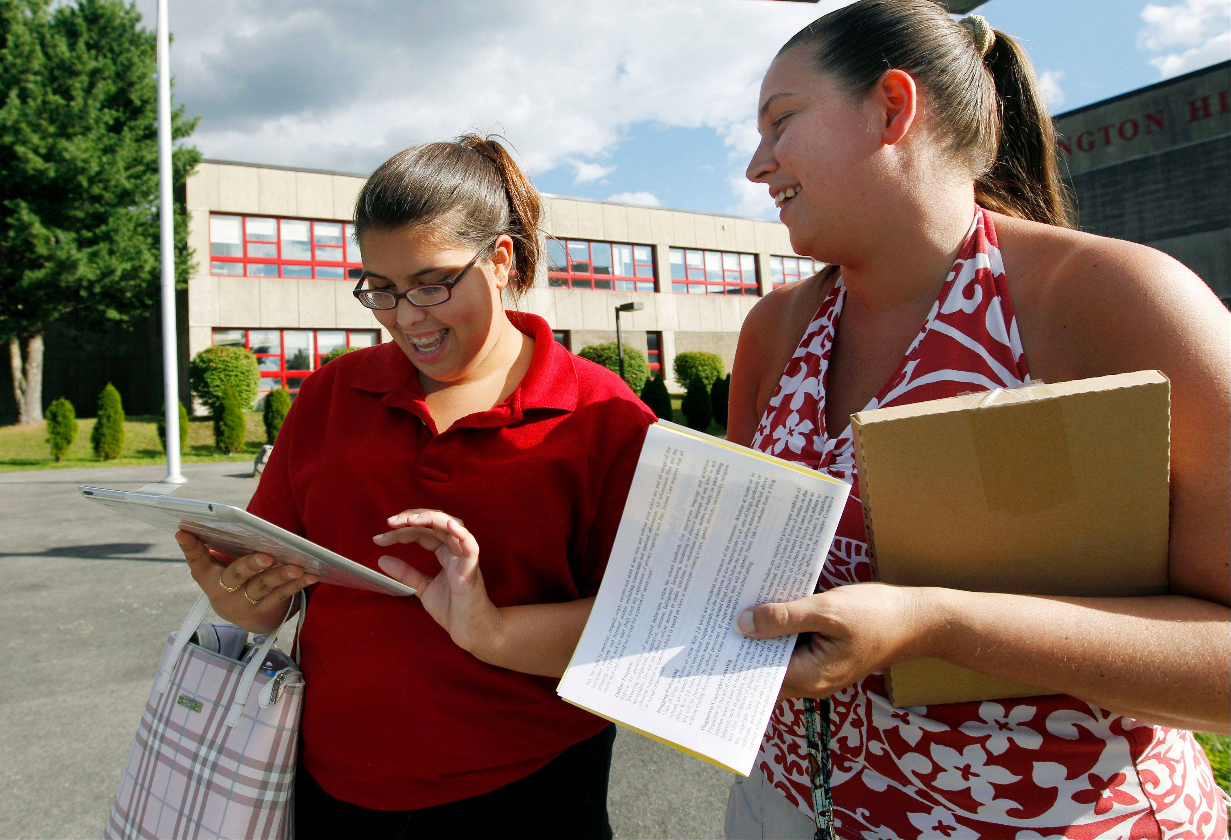 Senior Sabrina Pereira, 17, left, and her mother, Joanne Sullivan, check out her new iPad outside Burlington High School in Burlington, Mass. Burlington is giving iPads this year to every one of its 1,000-plus high school students. Some classes will still have textbooks, but the majority of work and lessons will be on the iPads.