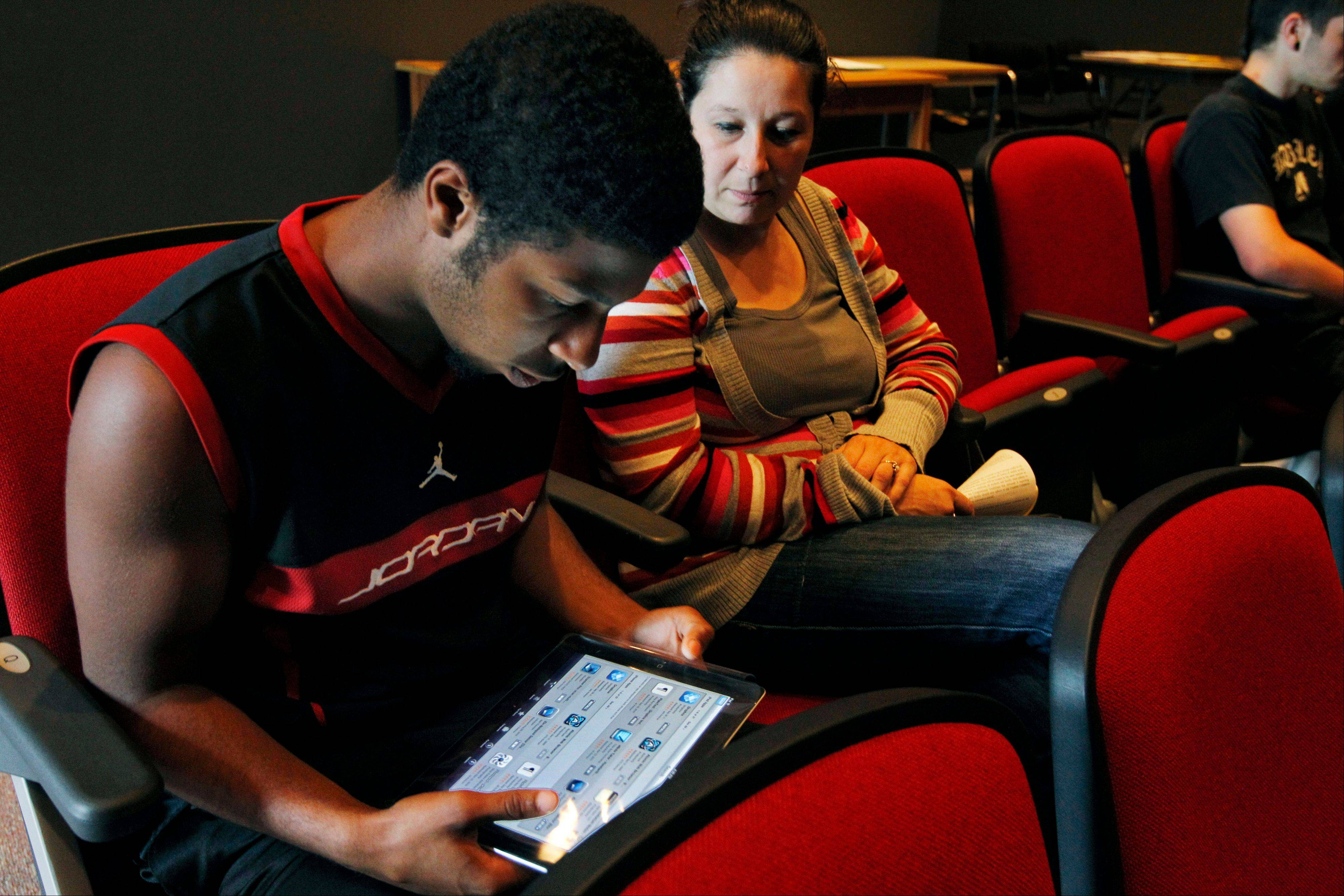 Sophomore Lenny Thelusma, 16, checks out his new iPad as his mother, Tara Killion, looks on at Burlington High School in Burlington, Mass. Burlington is giving iPads this year to every one of its 1,000-plus high school students. Some classes will still have textbooks, but the majority of work and lessons will be on the iPads.