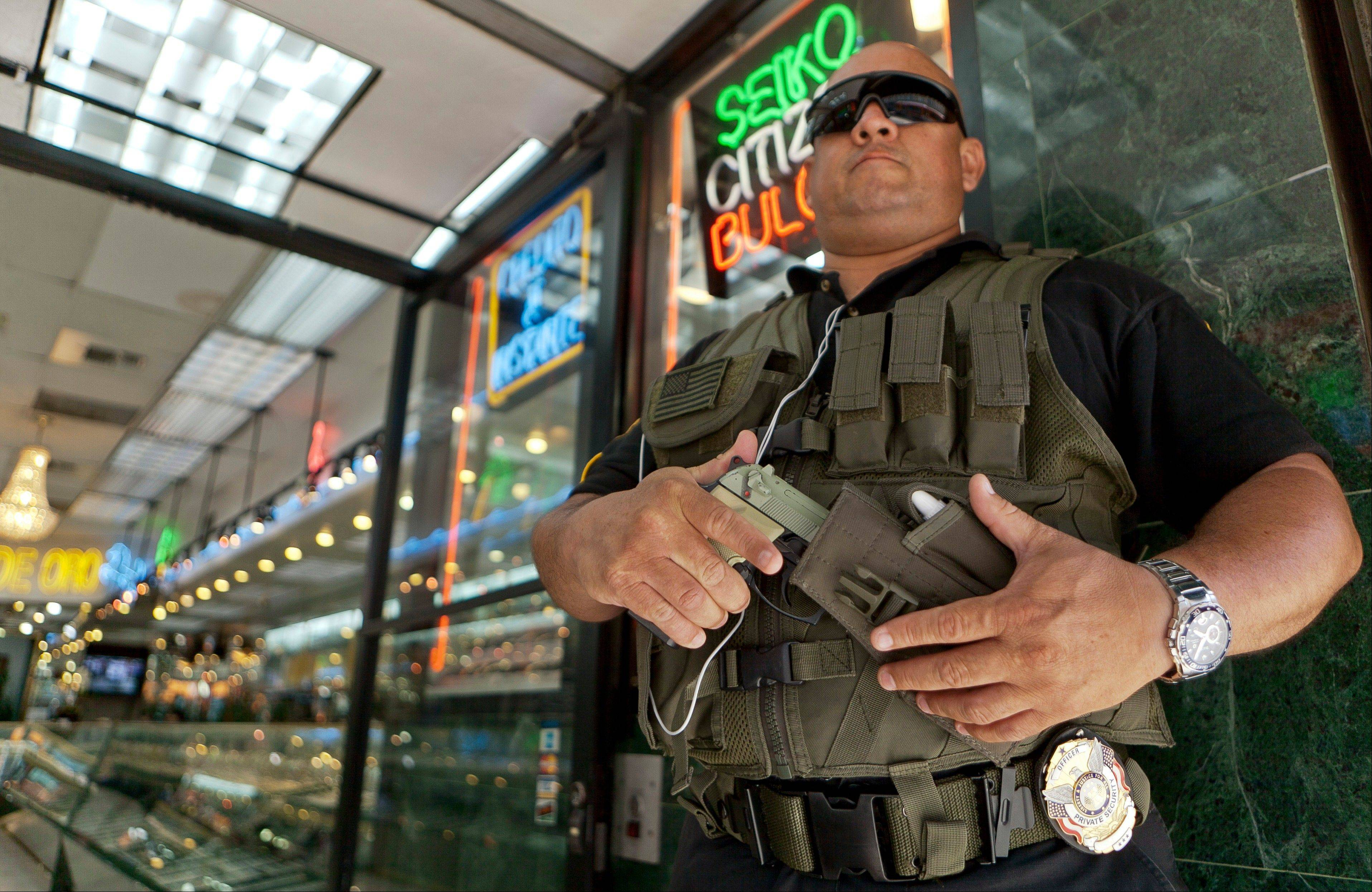 "Private security guard Gus Rodriguez stands outside ""El Palacio de Oro"" jewelry store in downtown Los Angeles. It's just one aspect of the gold fever now sweeping the country's criminal world. Law enforcement officials across the nation and beyond say they are seeing an uptick in robberies that correlates with golds record-high prices."