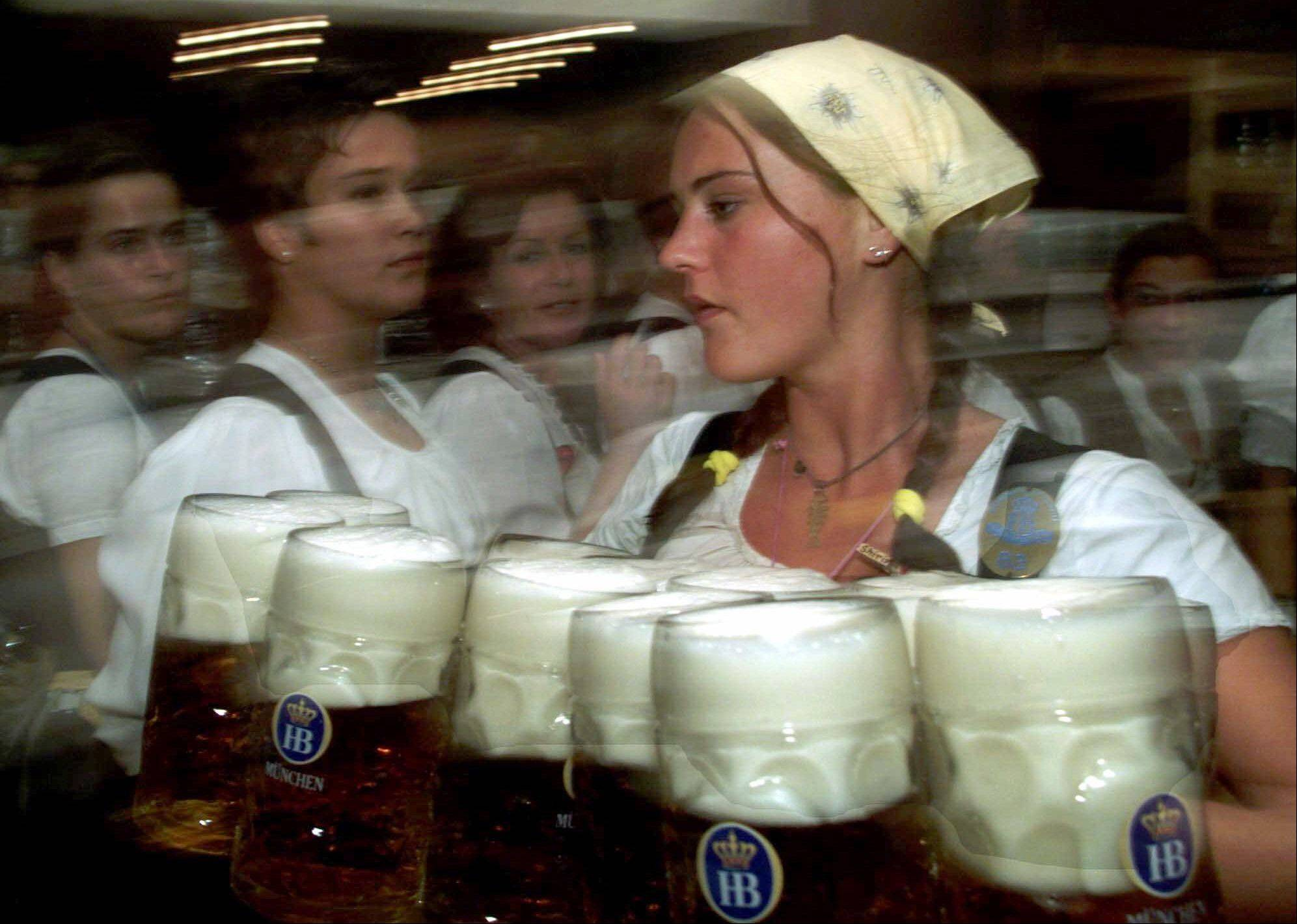 A waitress carries beer steins after the official Oktoberfest opening ceremony in Munich, Germany. Millions enjoy Oktoberfests in Europe and the United States each fall.