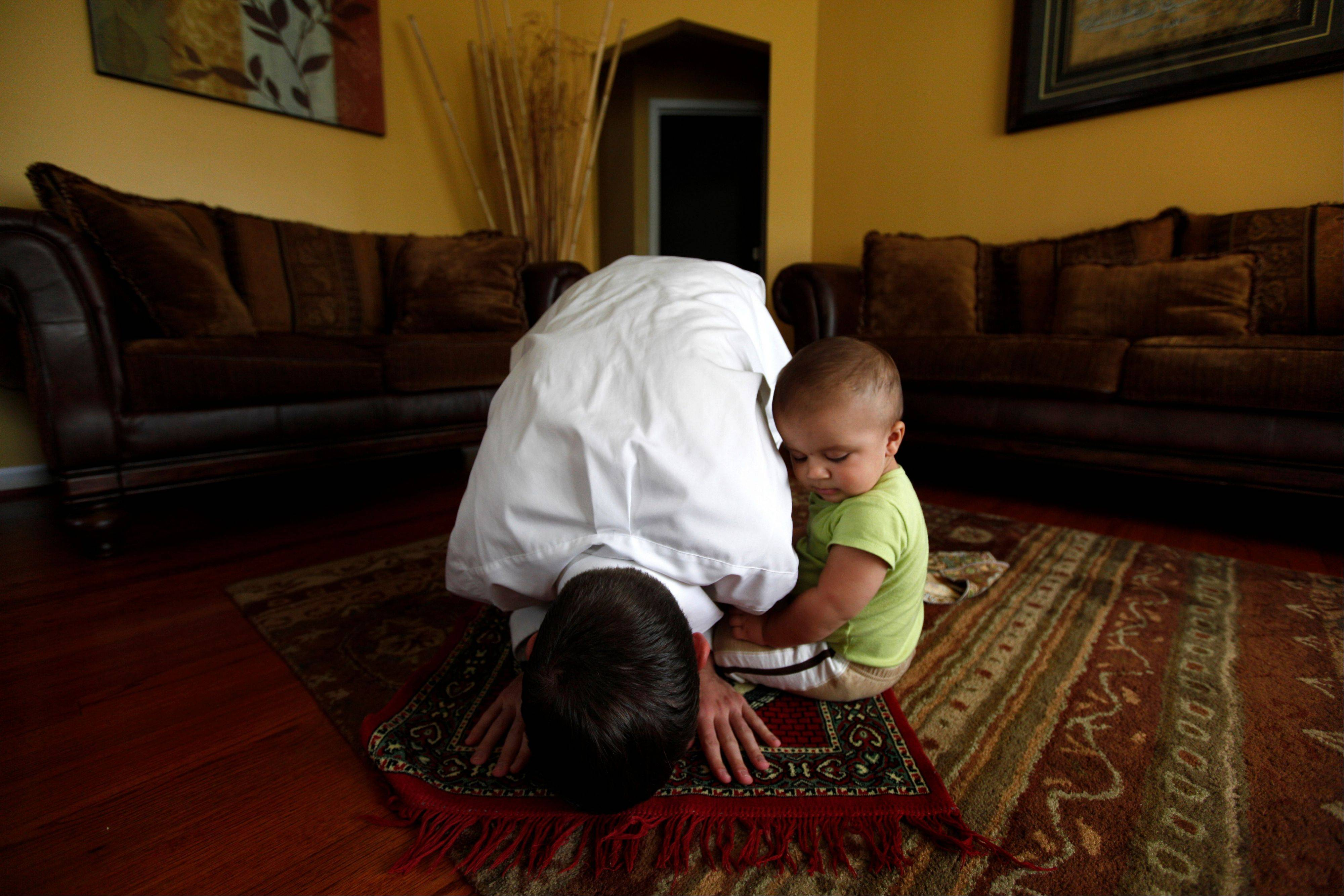 "Caleb Carter, 26, prays with his son Mahdi, 10 mo., at home in Dearborn, Mich. For Carter, the road to becoming a Muslim took years, but Sept. 11, 2001 was a turning point — specifically a high school teacher's hostile reaction that day to the terrorist attacks. ""I was a junior in high school at the time, taking a class called Nonwestern World Studies,"" said Carter, who then lived in Columbia, Mo., but now resides in the Detroit suburb of Dearborn, home to one of the nation's largest Muslim communities. ""For him, it was purely, 'This is what Islam teaches. We shouldn't be surprised.' He played the whole ëIslam equals terrorism card."""