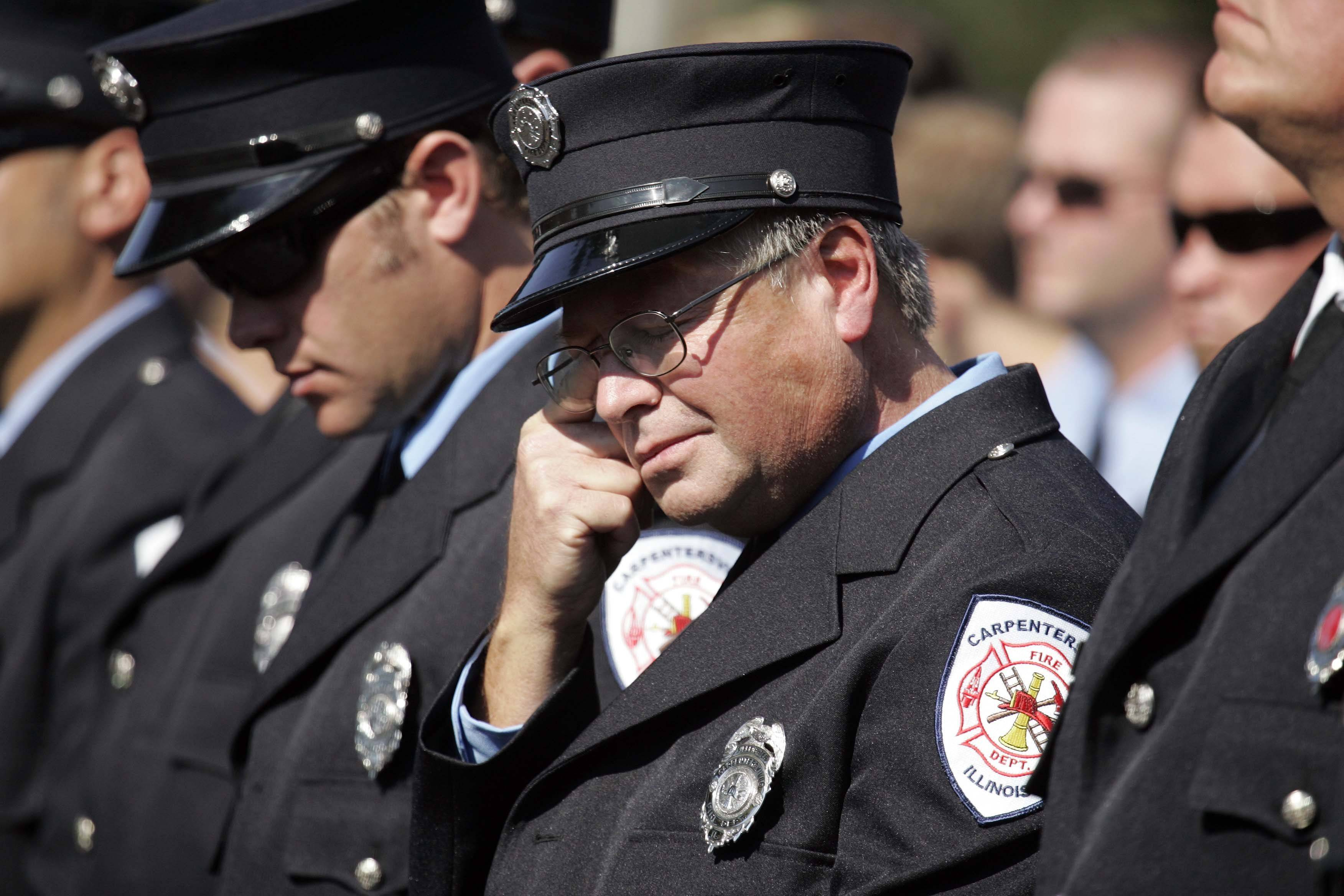 Carpentersville Firefighter Craig Lauer wipes away a tear during the Carpentersville Fire Department's dedication of their firefighter and 9/11 memorial Sunday, September 11, 2011.