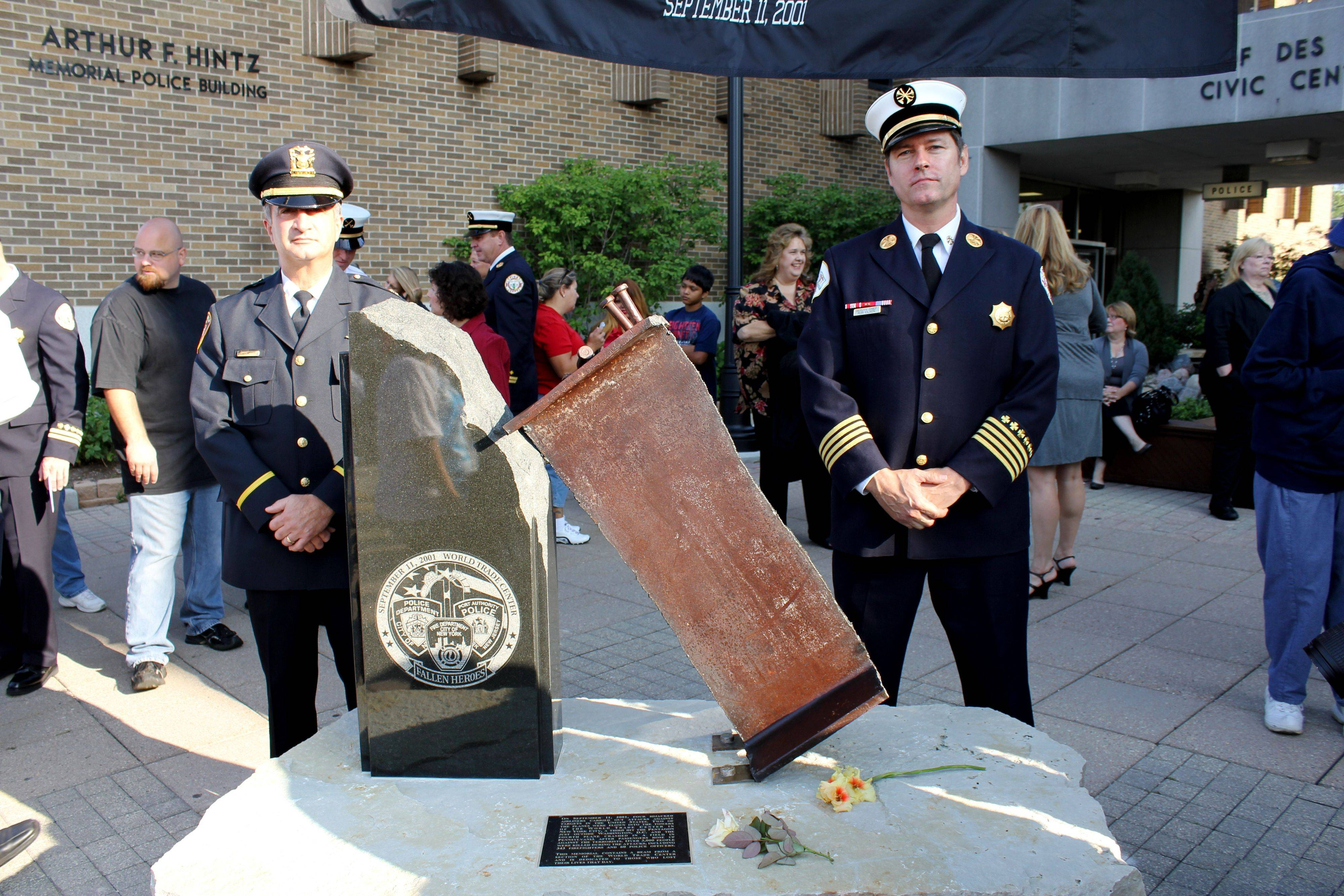 Des Plaines Police Cmdr. Nick Treantafeles and Fire Department Deputy Chief Ron Eilken stand behind the 114-pound beam salvaged from ground zero, which they were instrumental in bringing to Des Plaines. About 500 people attended the 9/11 commemoration Sunday.