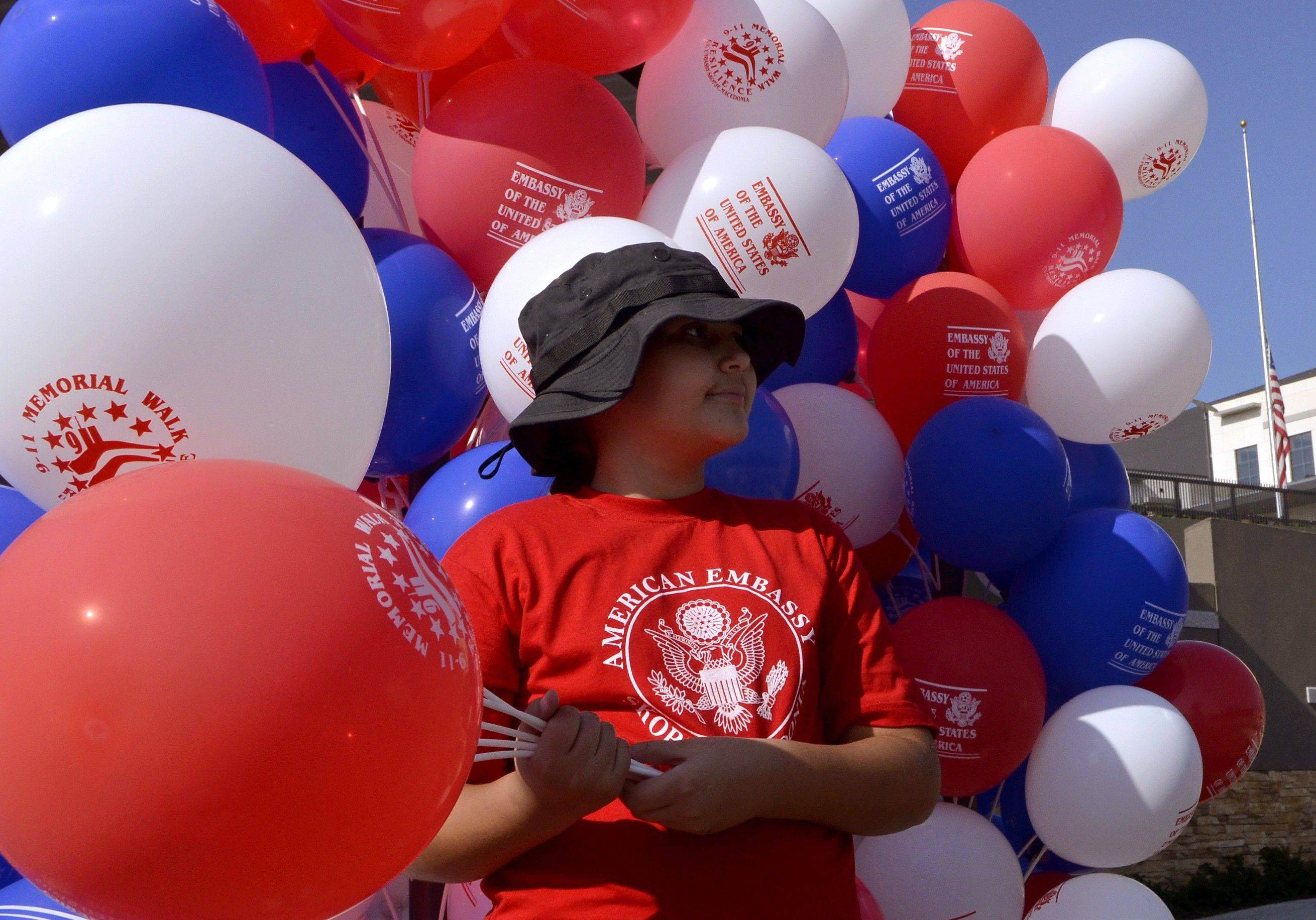 A girl holding balloons looks on in front of the U.S. Embassy compound in Macedonia's capital Skopje, on Sunday, Sept. 11, 2011. U.S. Embassy community organized Sunday a Memorial Walk to honor the 9/11 victims, survivors and their families, marking the 10th anniversary of the terrorist attacks on the United States. (AP Photo/Boris Grdanoski)