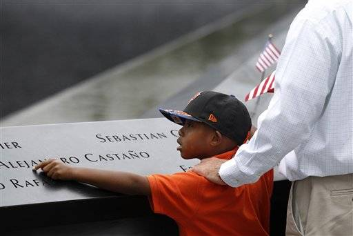 A young boy points to a name on the wall at the Sept. 11 memorial during the 0th anniversary observance of the terrorist attacks on the World Trade Center, Sunday, Sept. 11, 2011 in New York.