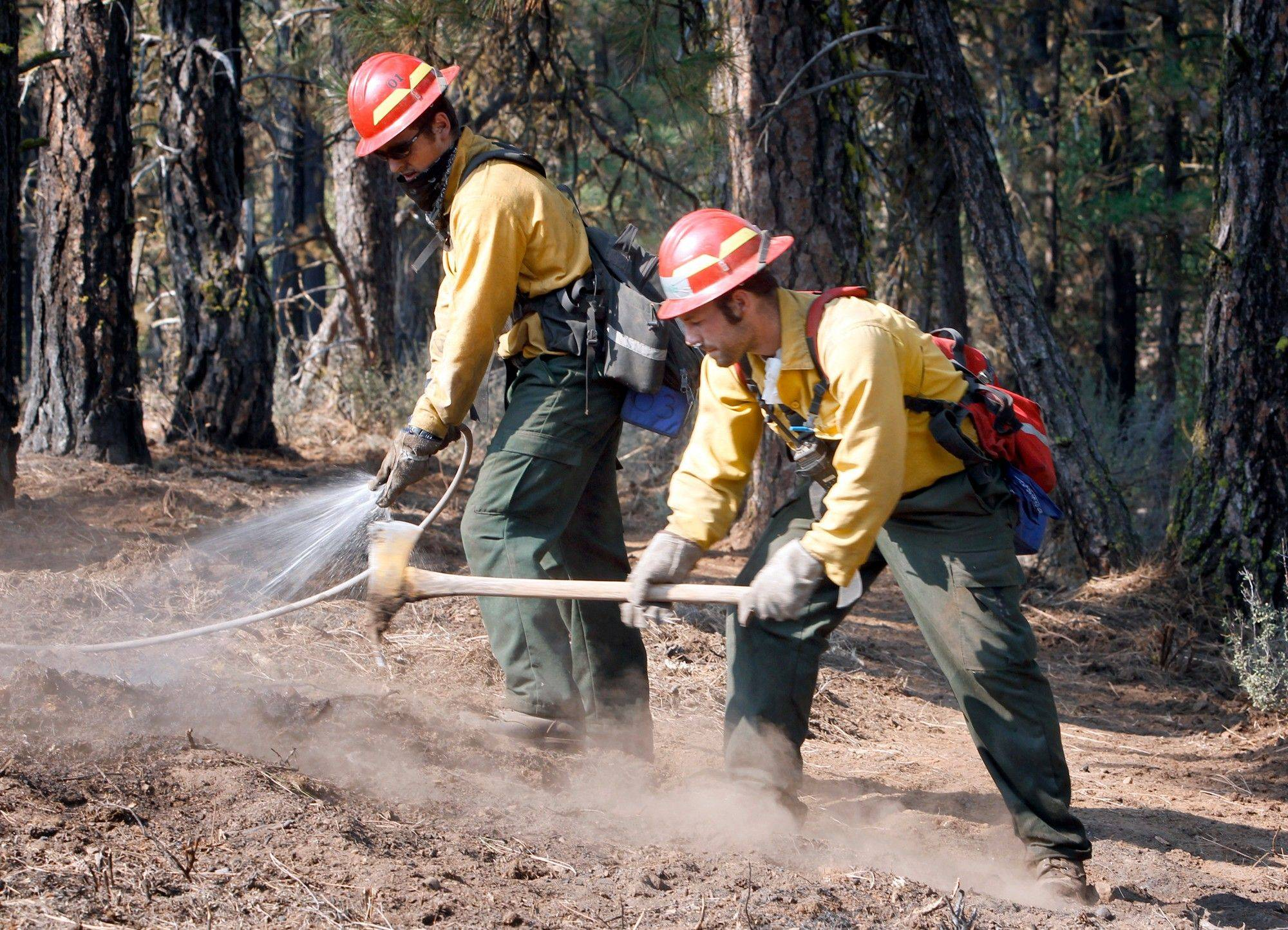 Alex George, left, and Kevin Weed of Glacier Peak Wildfire, Inc., extinguish hot spots along a fire line near Box Canyon Road on the eastern boundary of the Monastery Complex Fire, Saturday, Sept. 10, 2011 in Yakima, Wash.